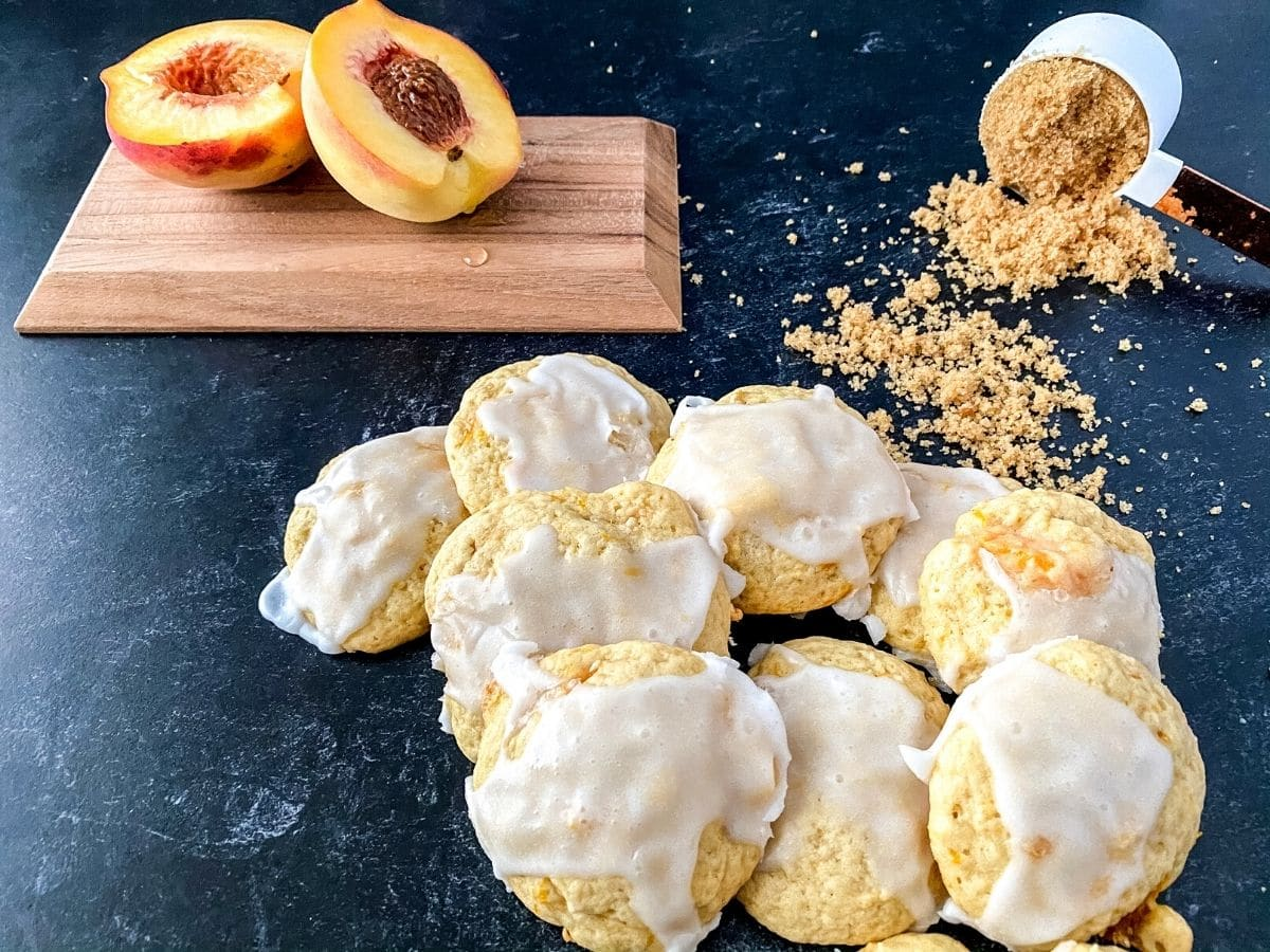 Cookies with glaze on counter next to cutting board with peach