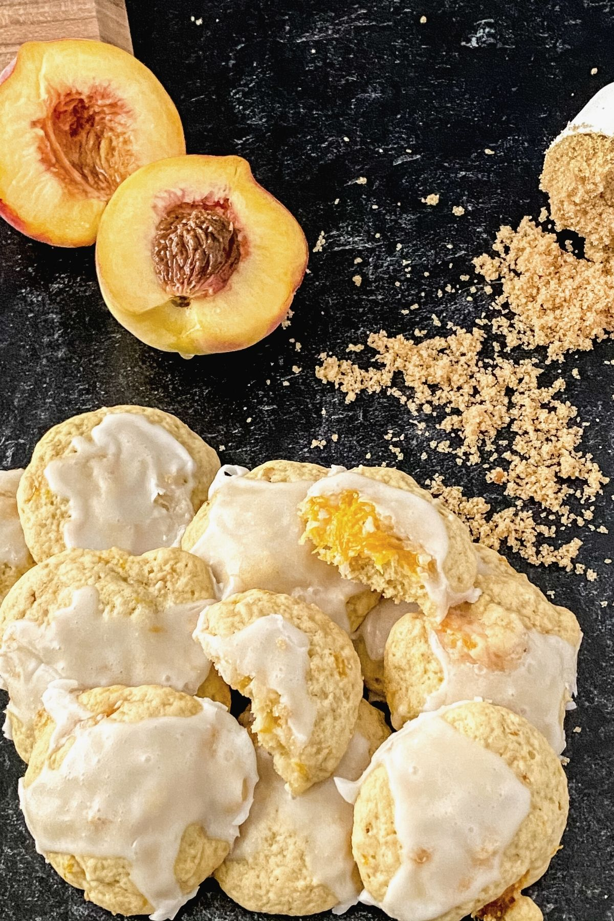 Looking down on stack of cookies with white glaze next to sliced peach