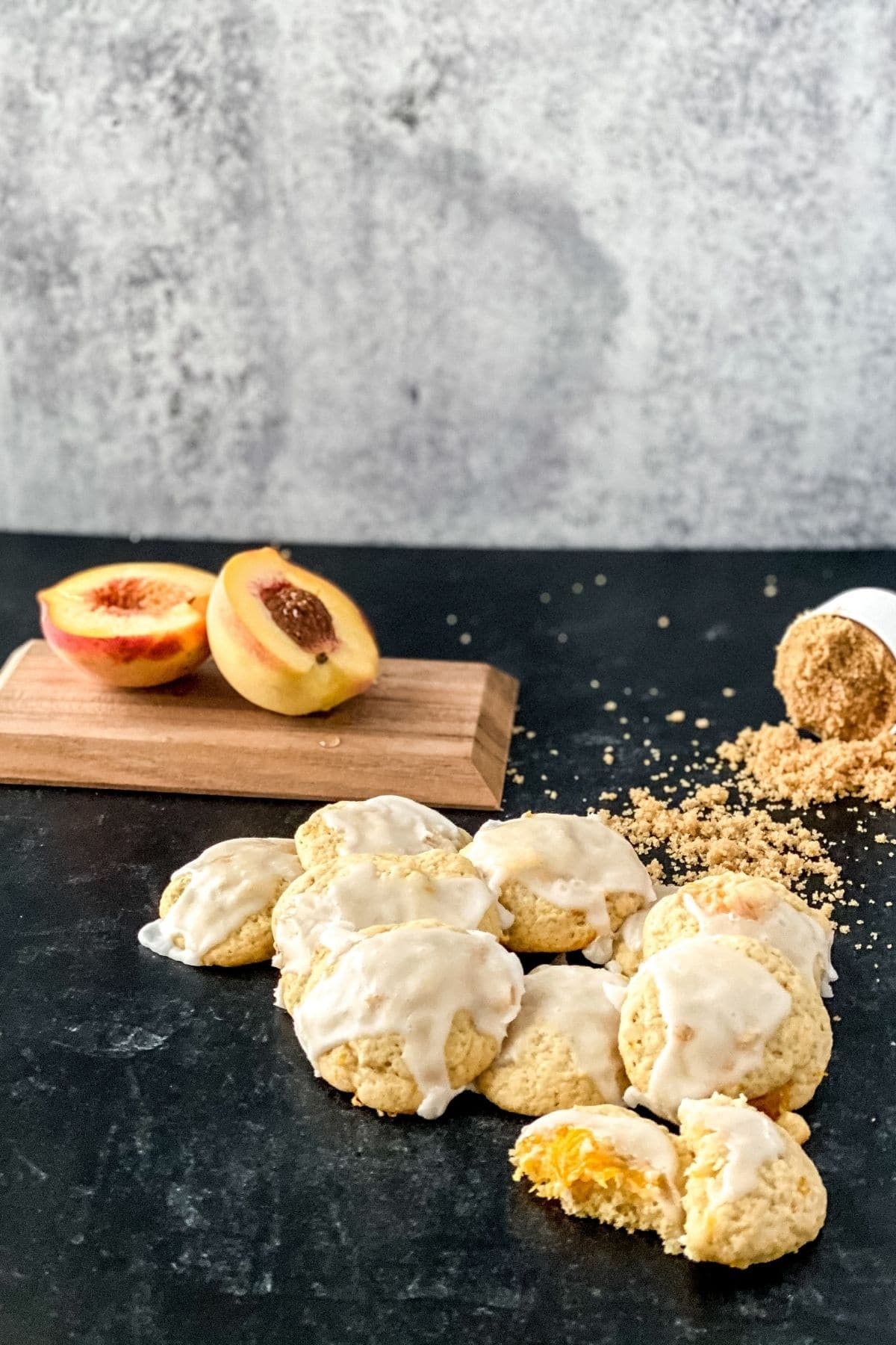 Cookies on black counter in front of cutting board with halved peach
