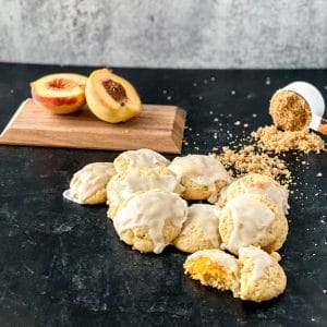 Peach cookies on black table with peach halved on cutting board