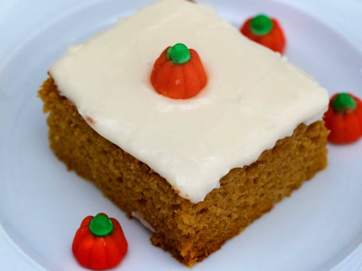 Slice of pumpkin sheet cake with cream cheese frosting and candy piece on top