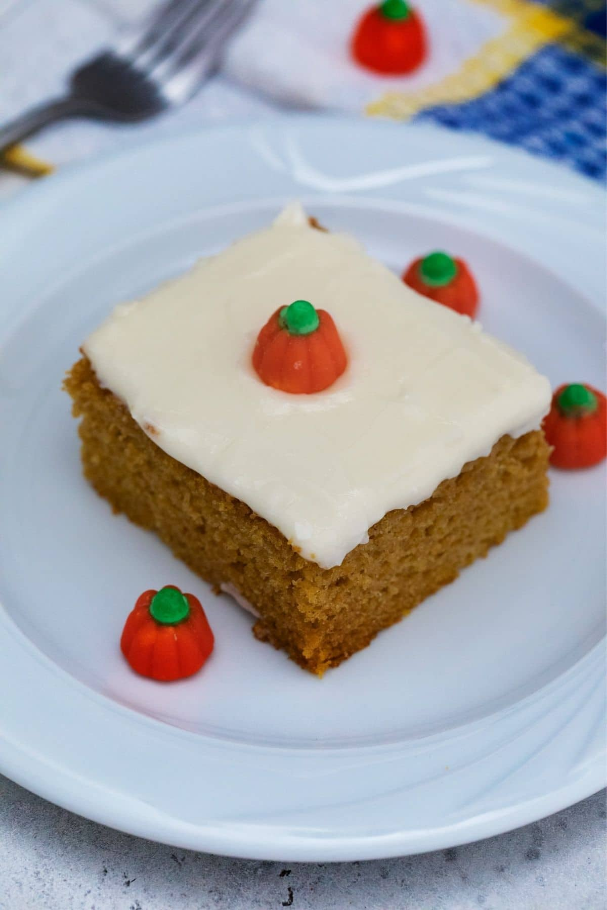 Square of cake on white saucer with pumpkin candy