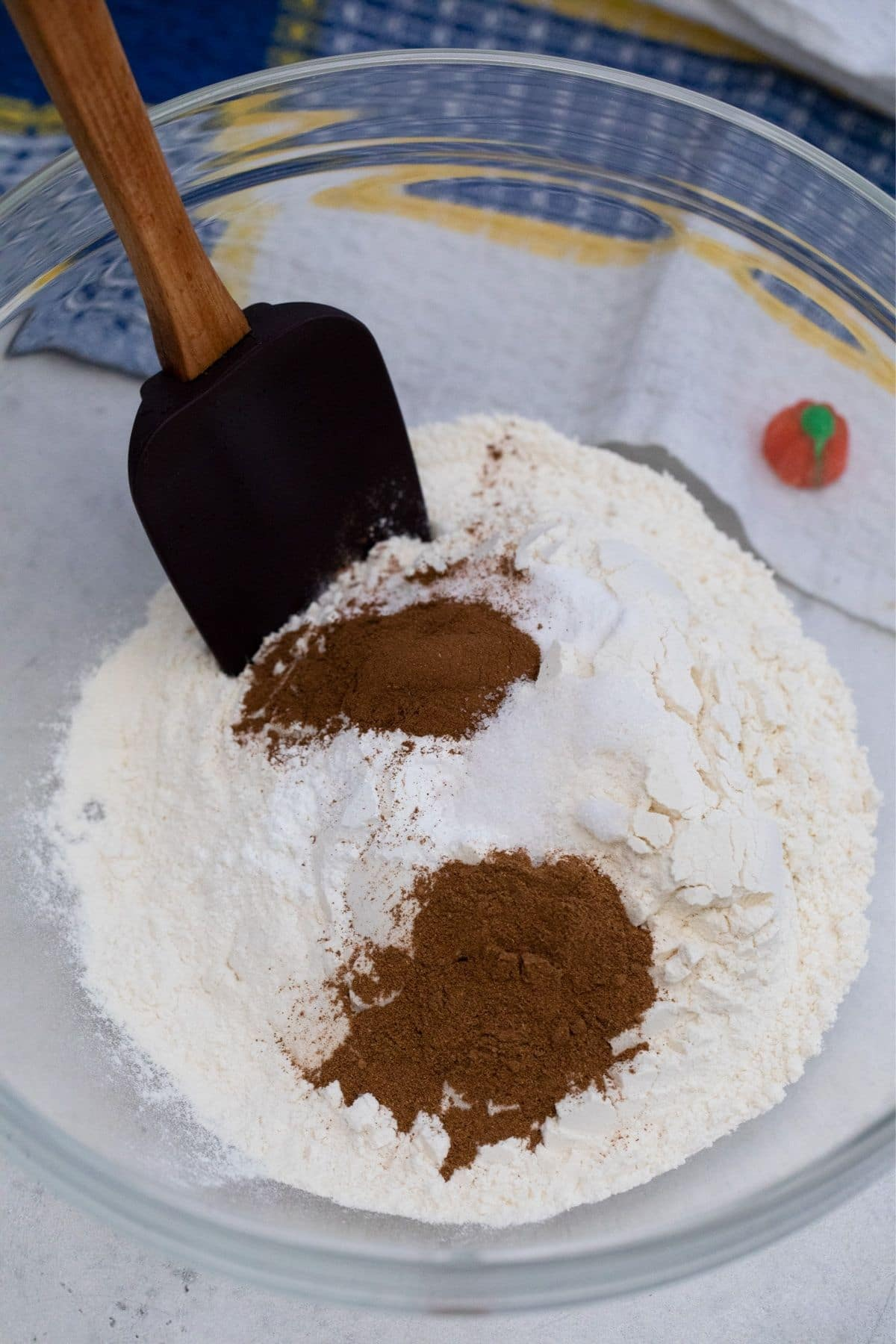 Black spatula in flour and spices in large glass bowl