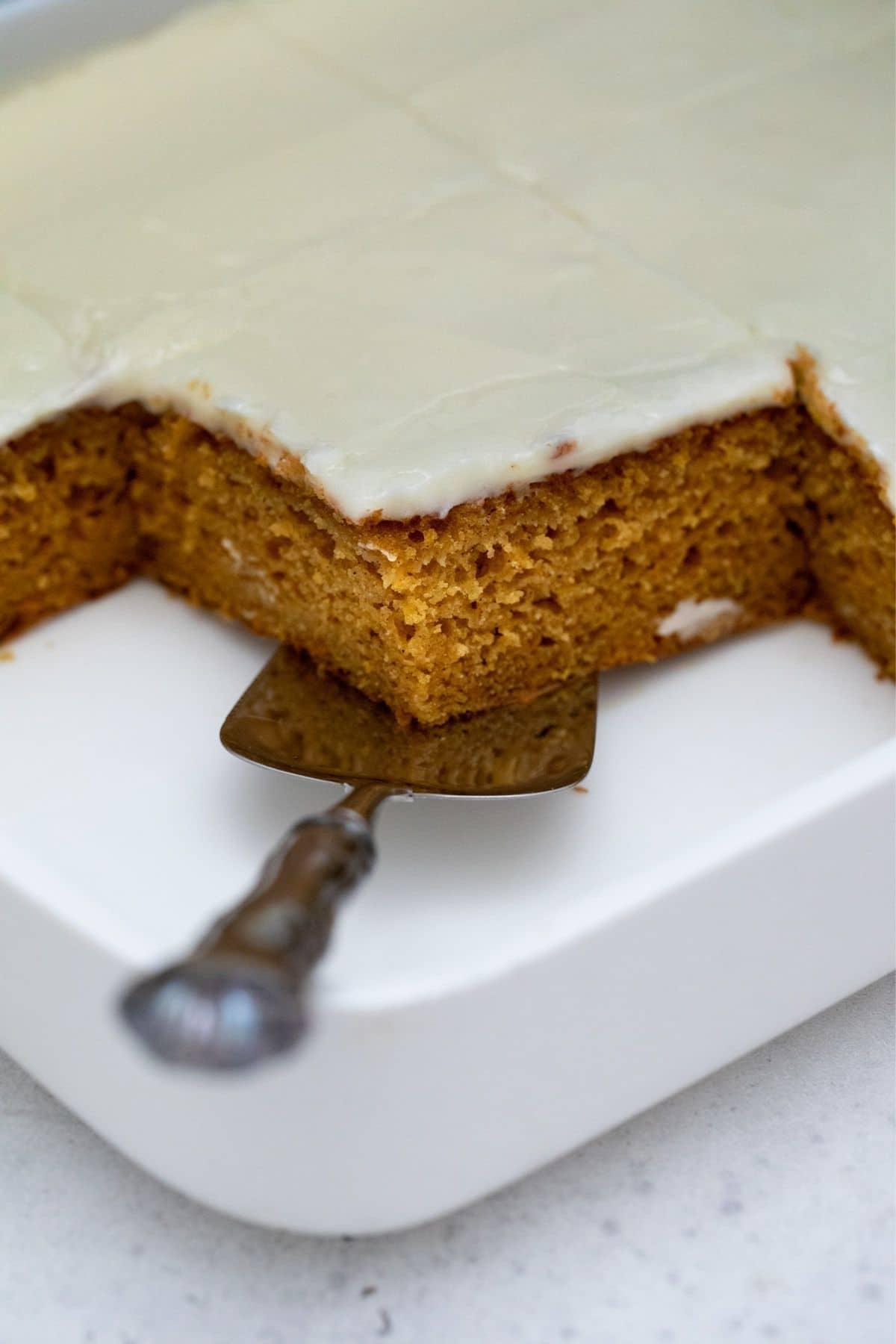 Metal spatula under cake slice in cake pan