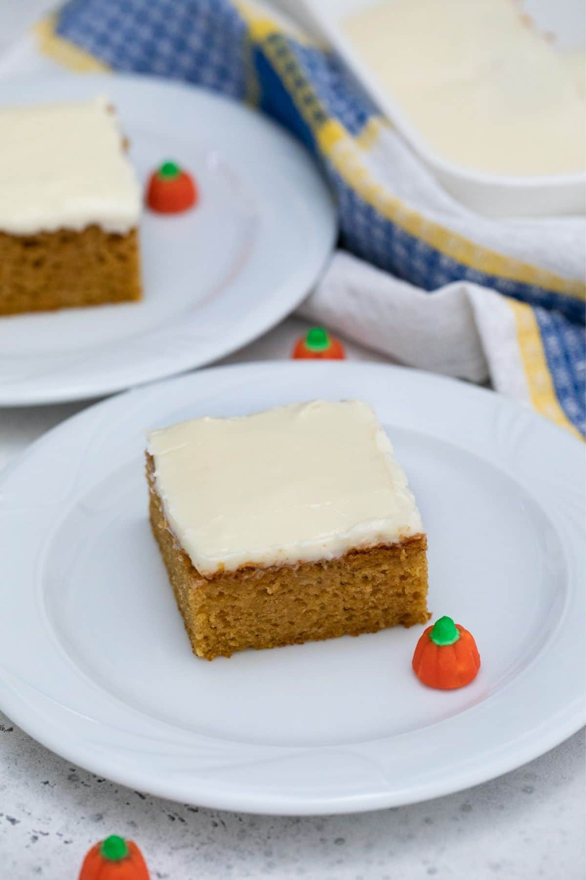 Two white plates with square of cake on each by blue napkin