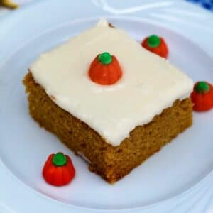 Cake slice on white saucer with pumpkin candies on plate