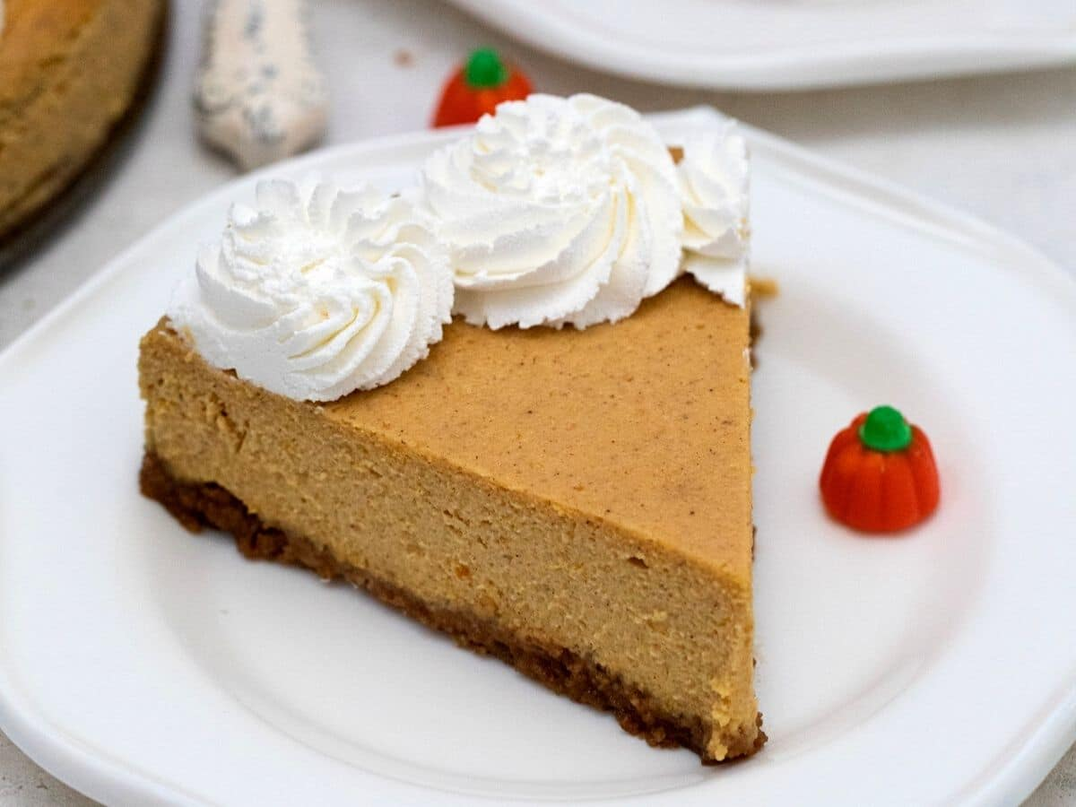 Cheesecake slice on white saucer holding pumpkin candy