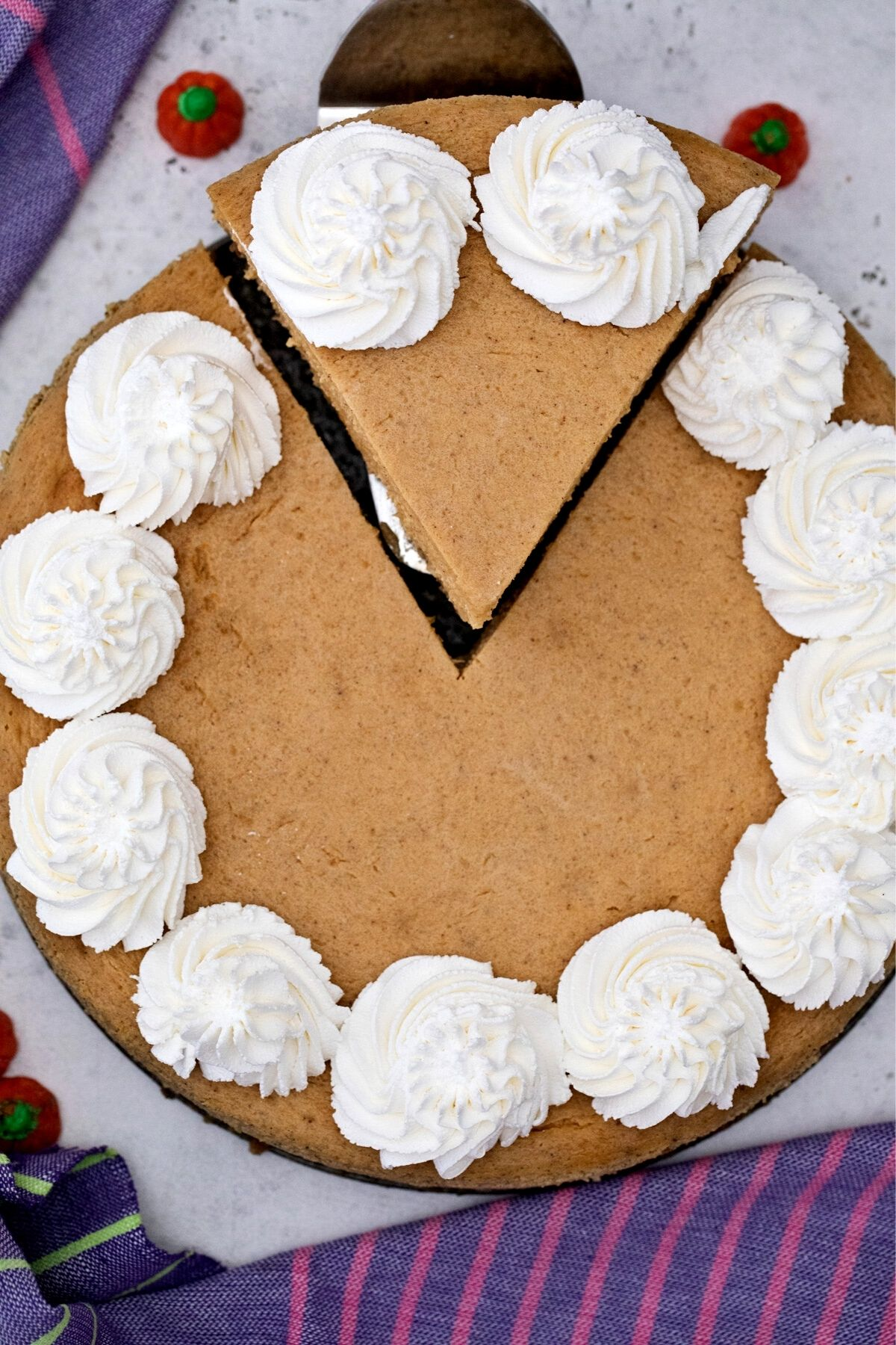 Whole cheesecake with whipped topping dollops and slice cut out