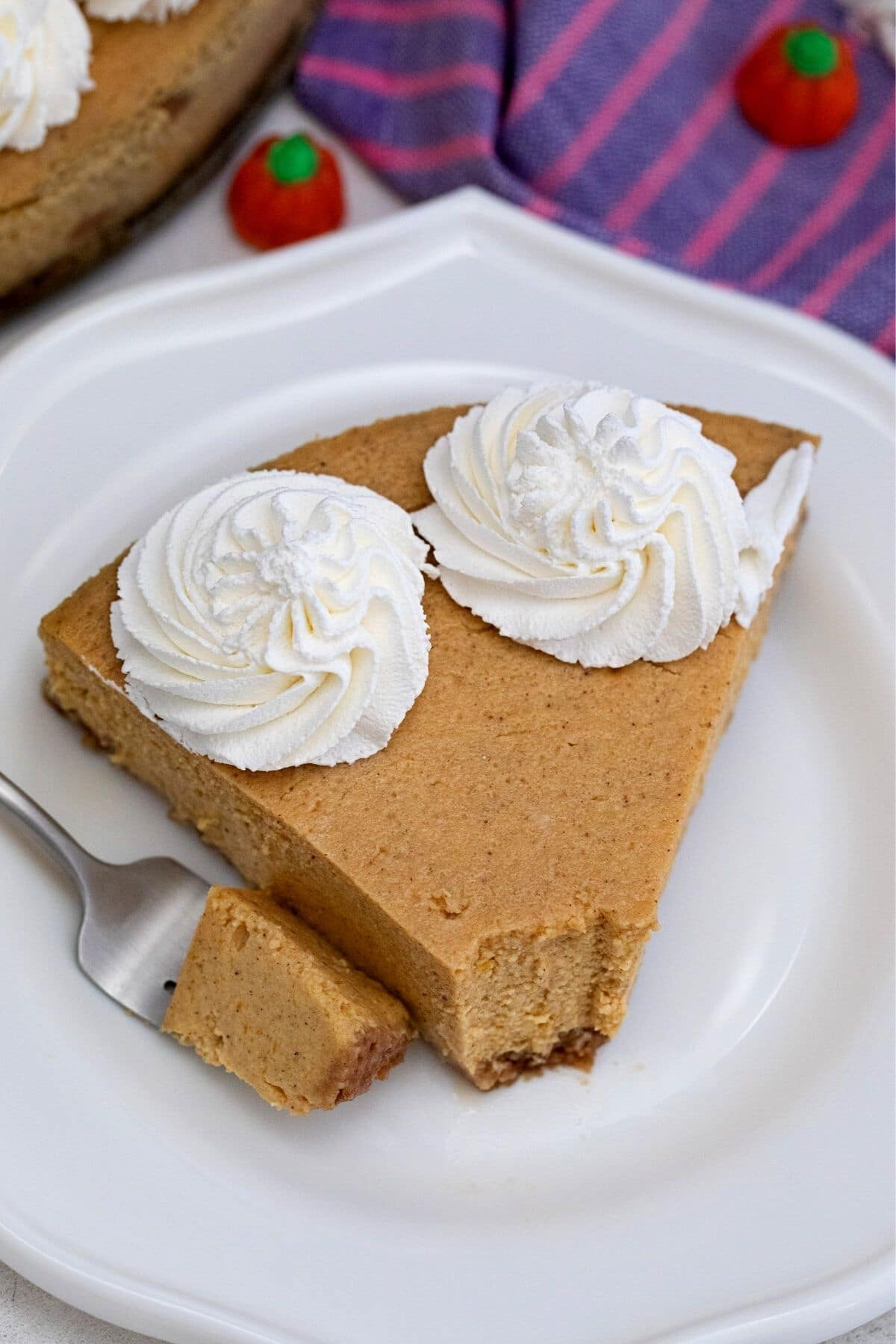 Bite of pumpkin cheesecake on fork by sliced cheesecake on white plate