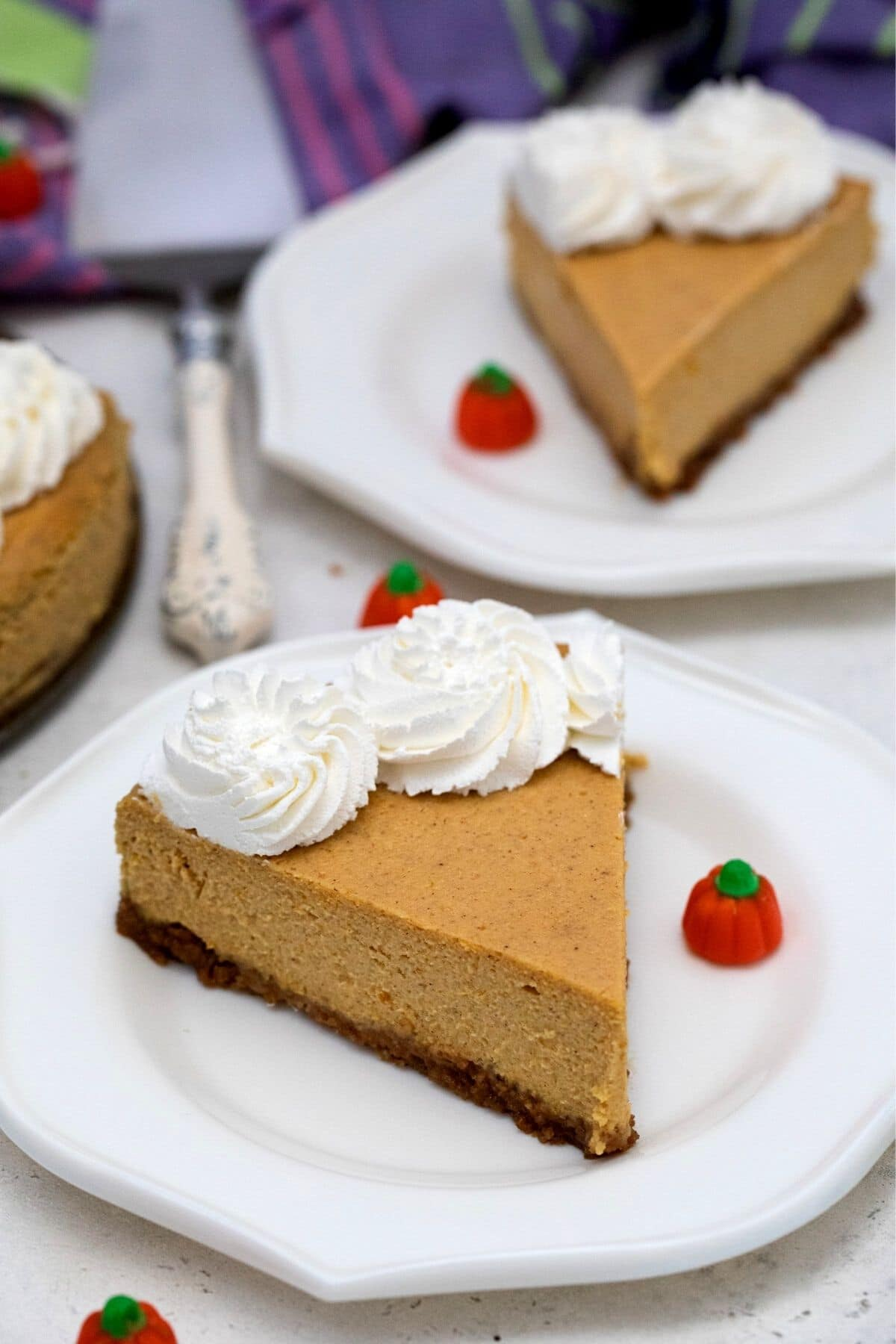 Slices of cheesecake with whipped topping on white saucers