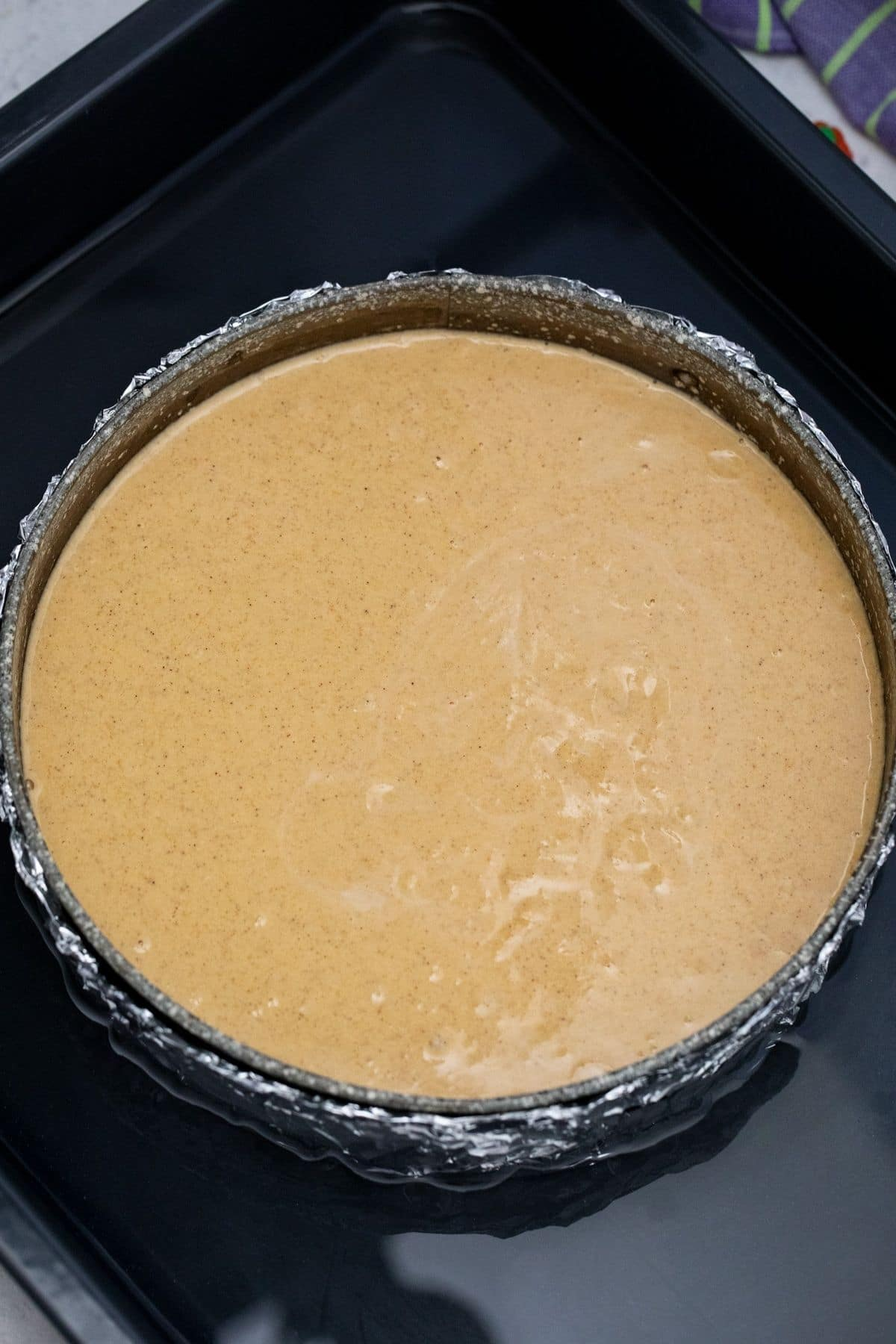 Large pan filled with water and springform pan of cheesecake in center