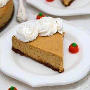 Single slice of pumpkin cheesecake on saucer with mini pumpkin candy