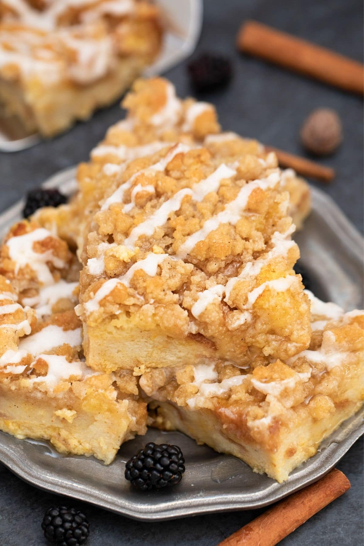 French toast bake squares stacked on black plate on table by cinnamon sticks