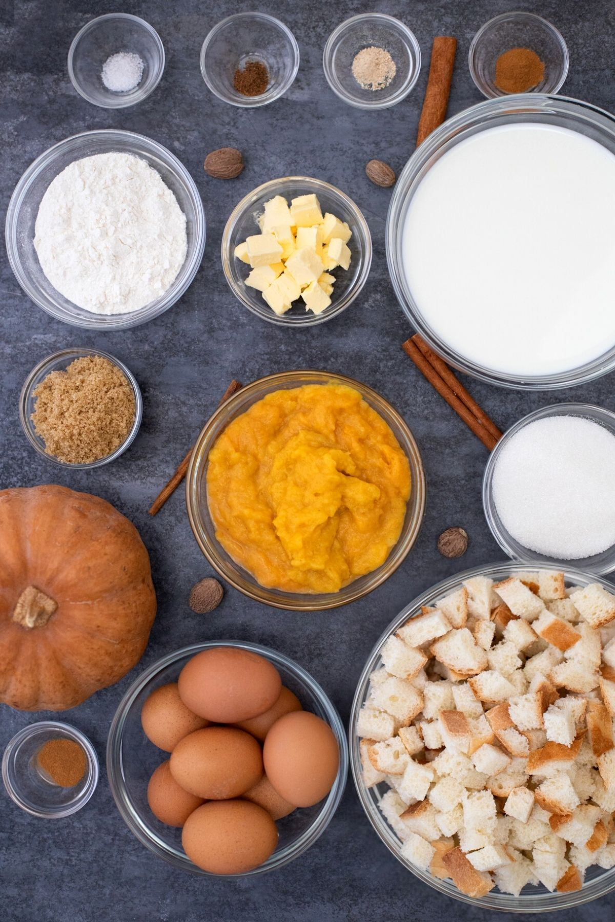 Ingredients for pumpkin spice french toast in glass bowls on gray table