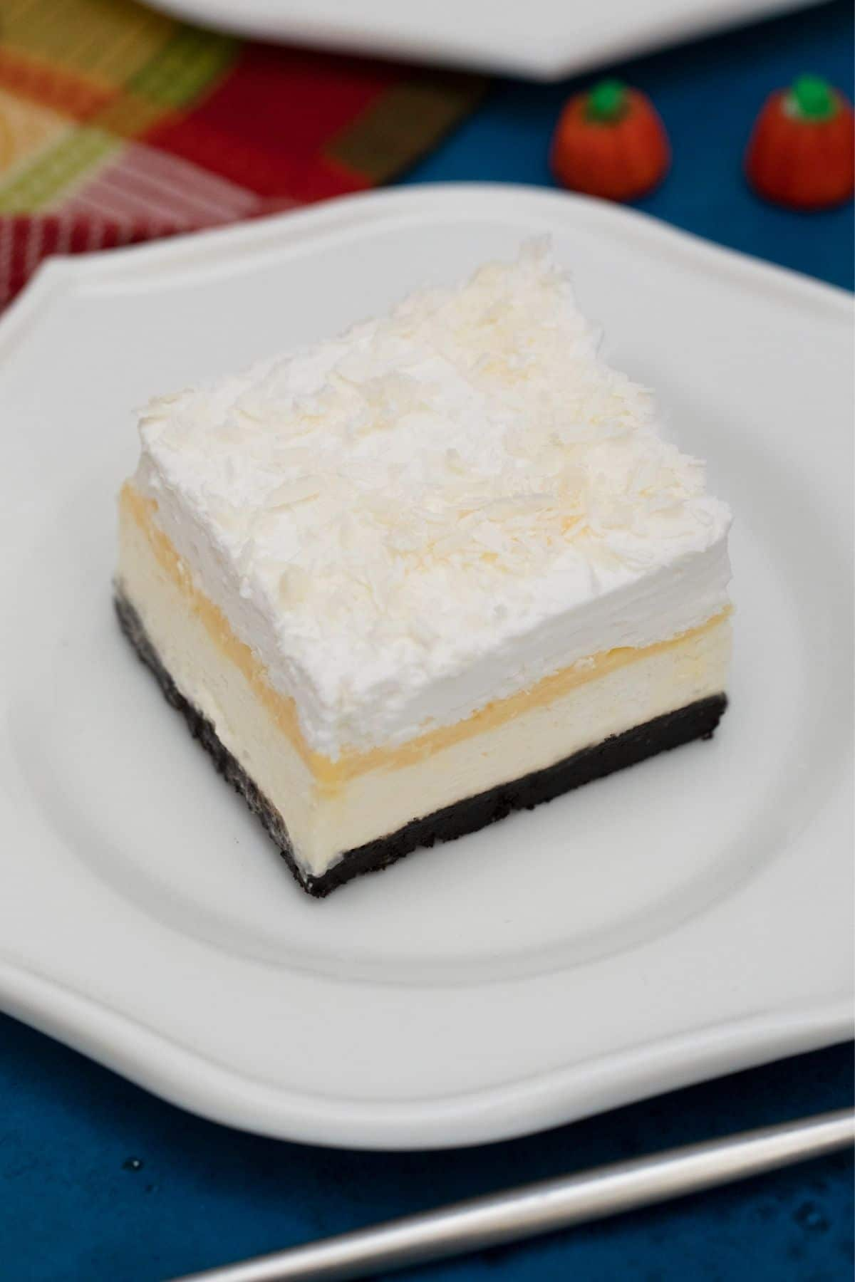 Slice of layered dessert on white plate sitting on blue table