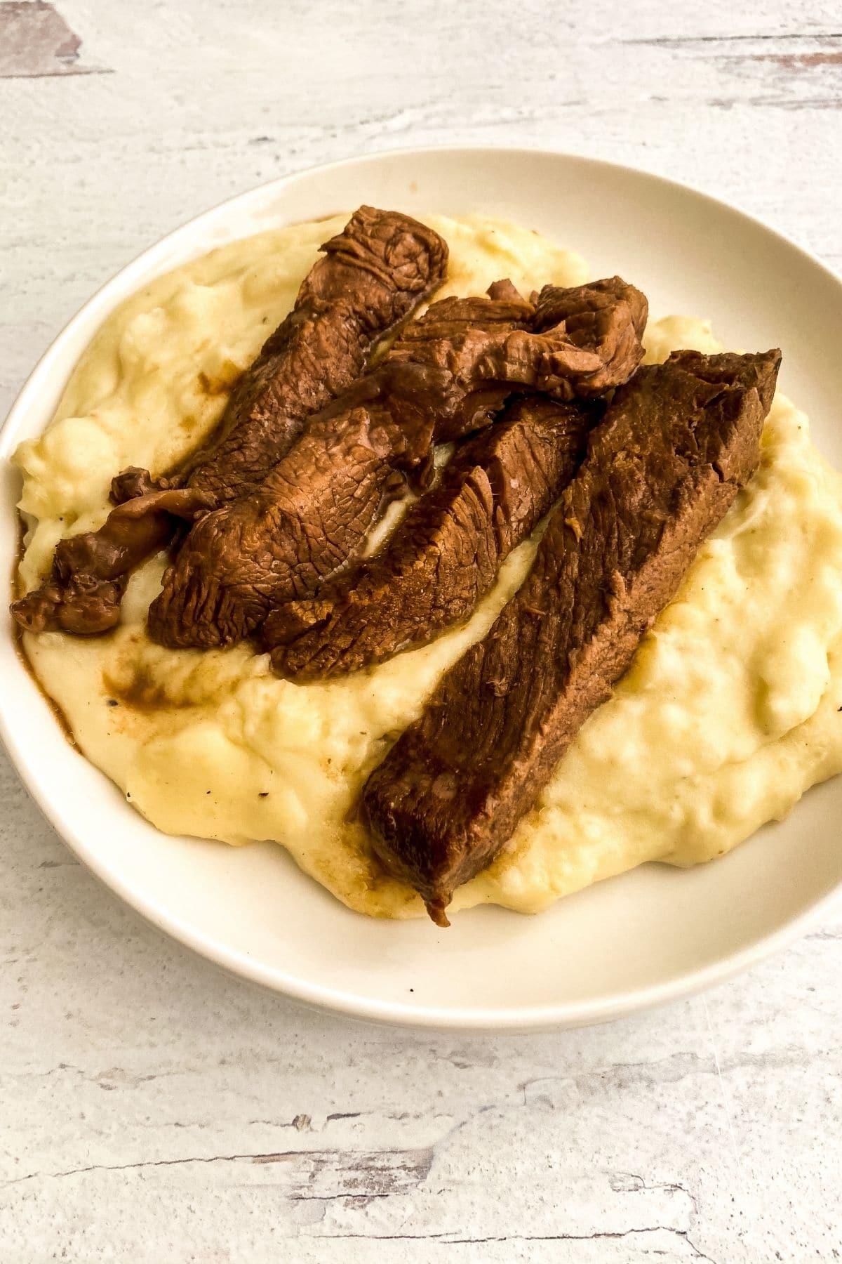 Large white bowl of mashed potatoes and steak