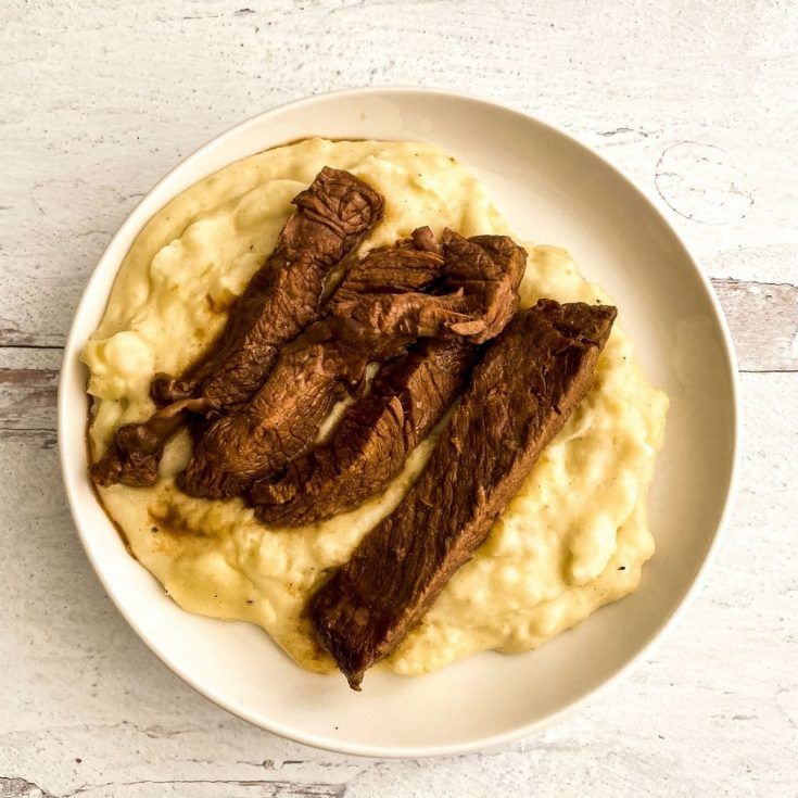 White bowl of mashed potatoes with steak on top