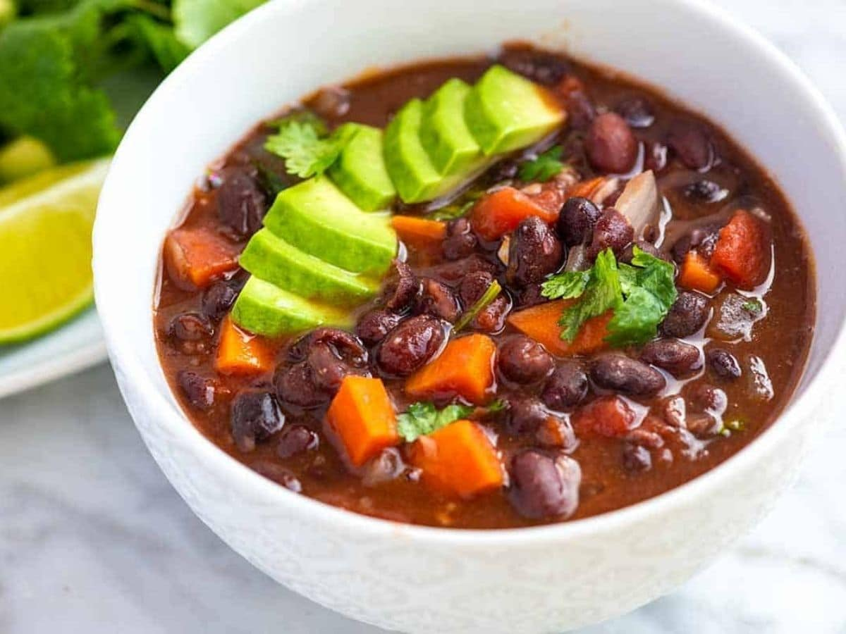 white bowl of bean soup with avocado on top