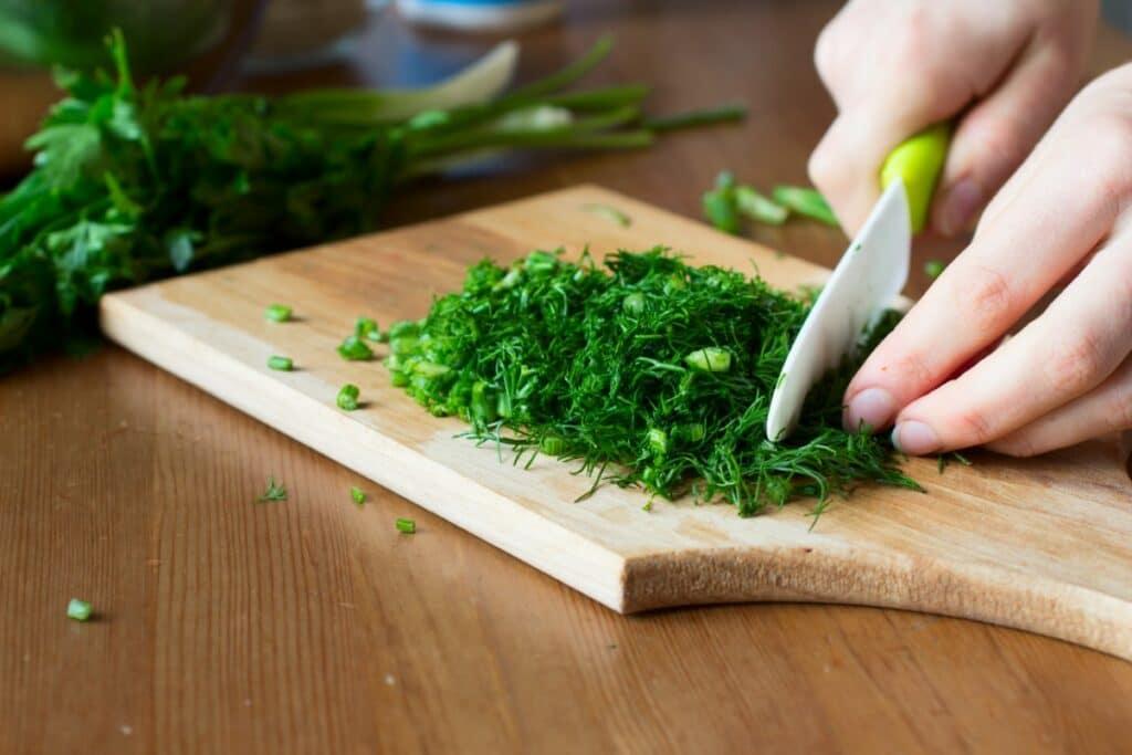 Chopping fennel greens using a ceramic knife.