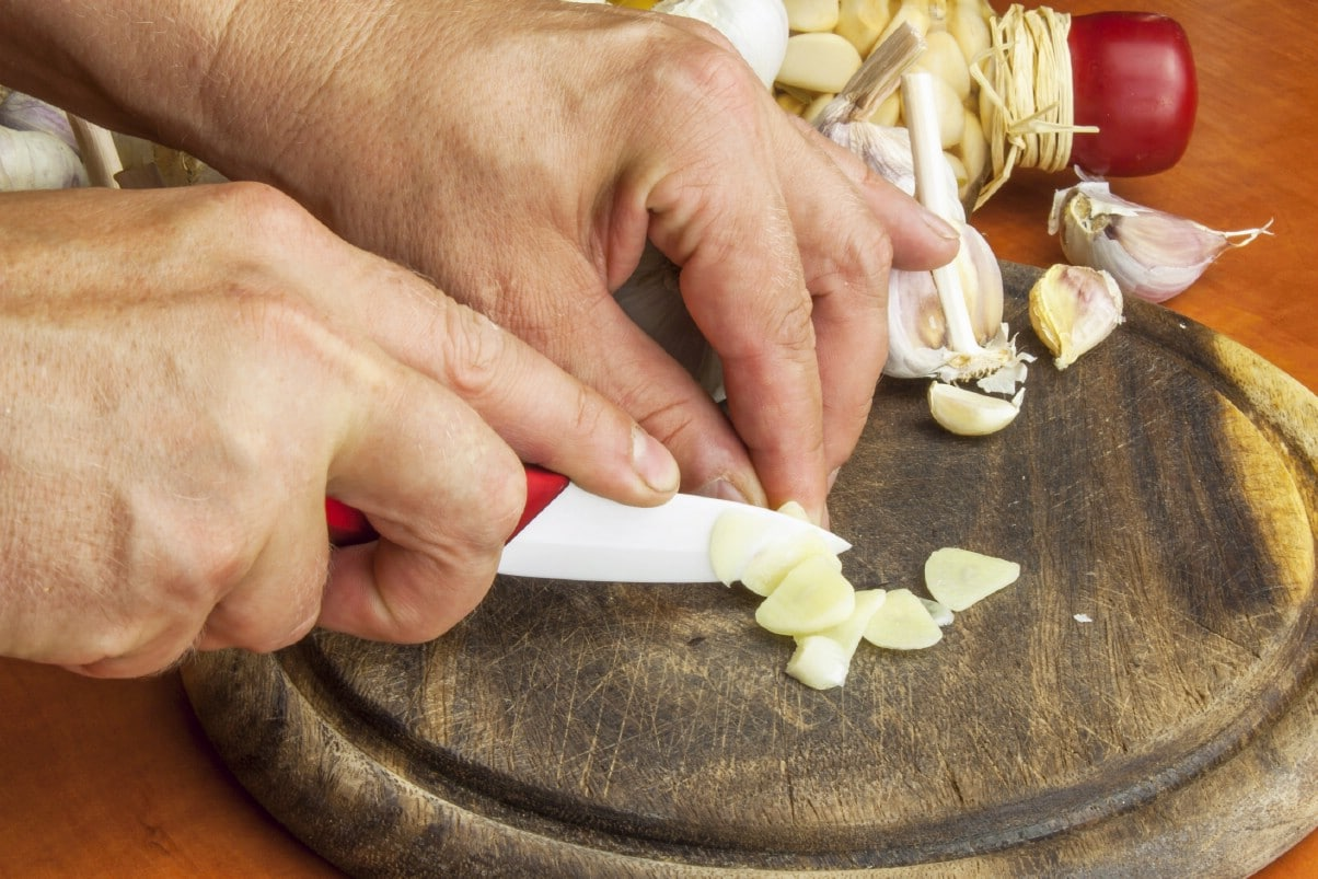chopping garlic with a small ceramic knive