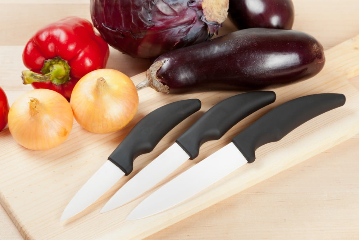 3 ceramic knives on a cutting board