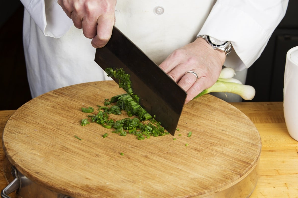 Cutting onion greens on a round cutting board with a chinese cleaver.