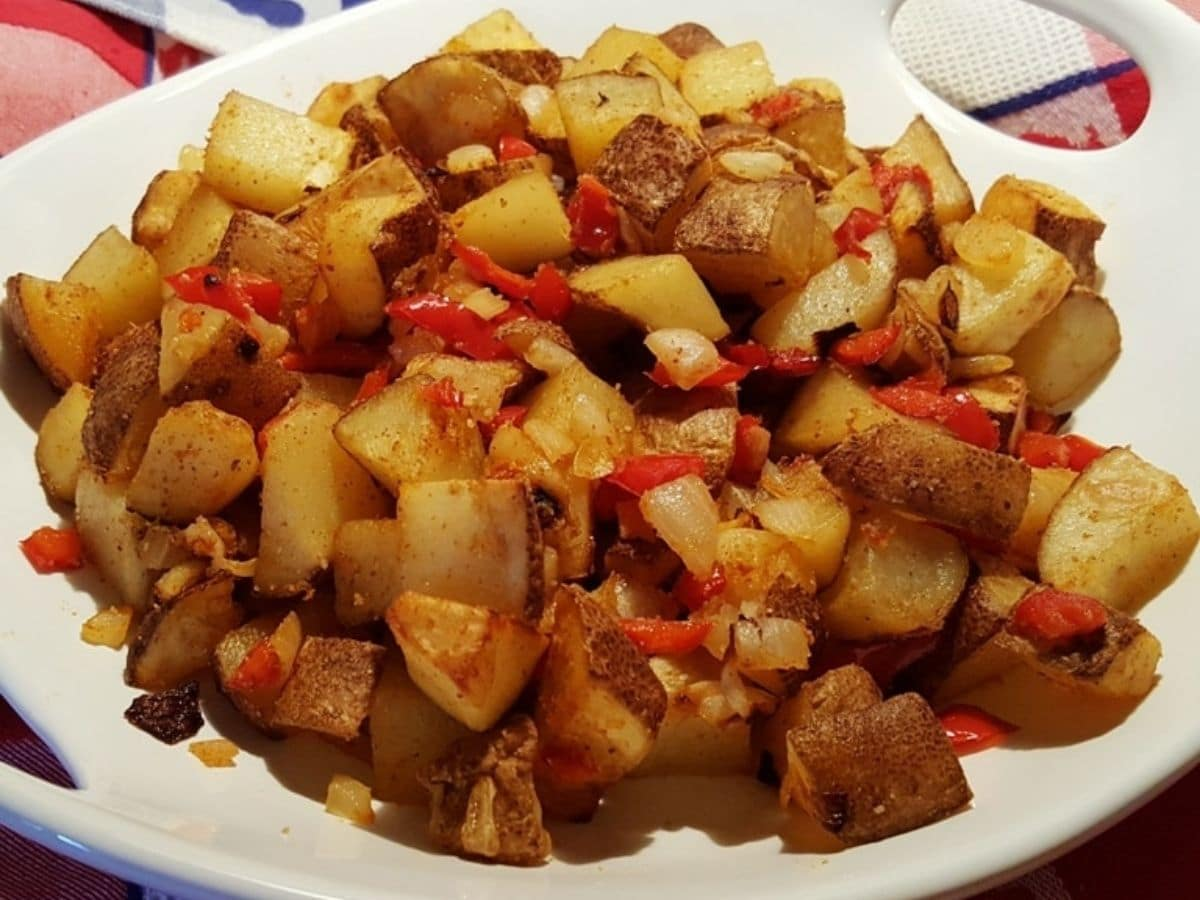 White plate of potatoes pieces with ketchup drizzle