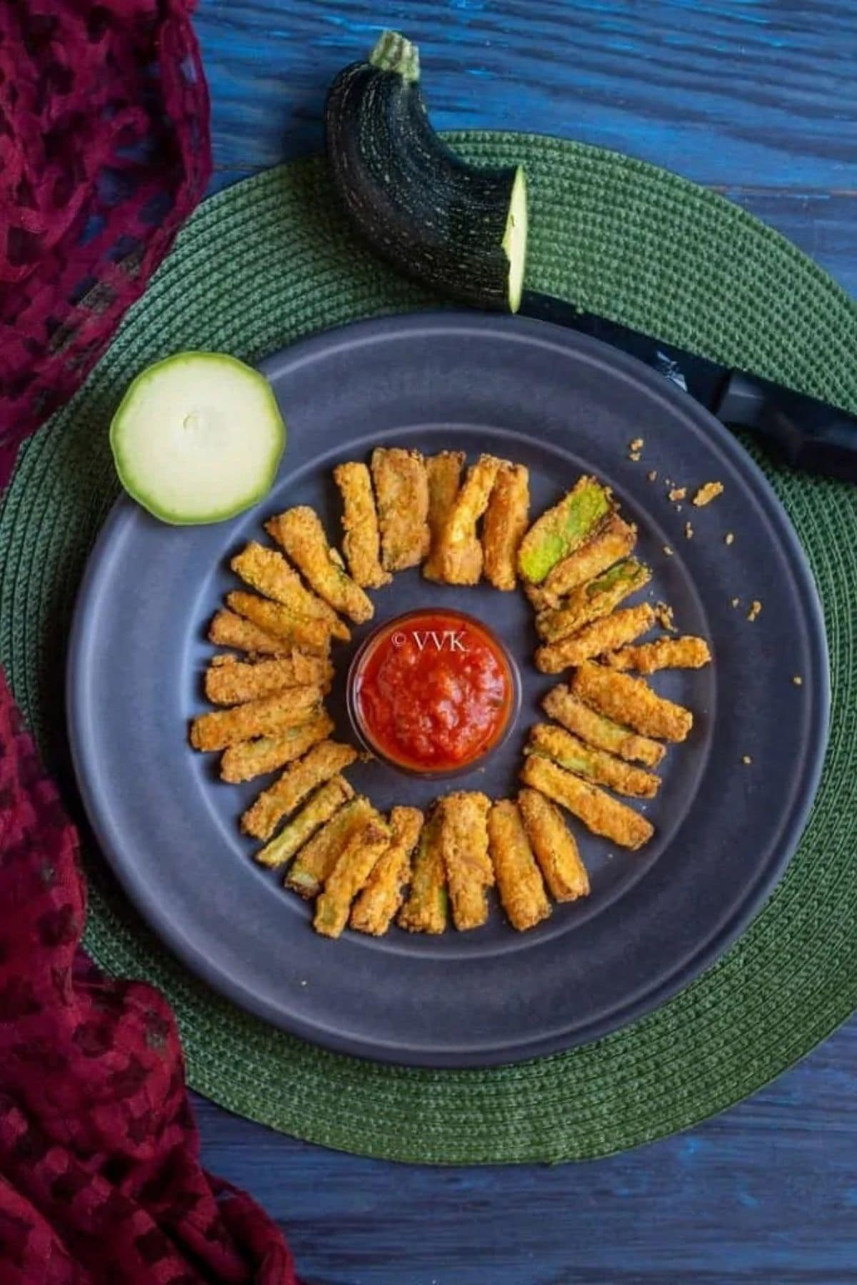 Zucchini fries in circle around bowl of ketchup on blue plate