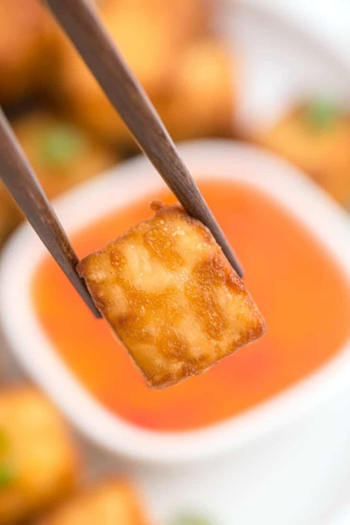 Chopsticks holding piece of toasted tofu above sauce