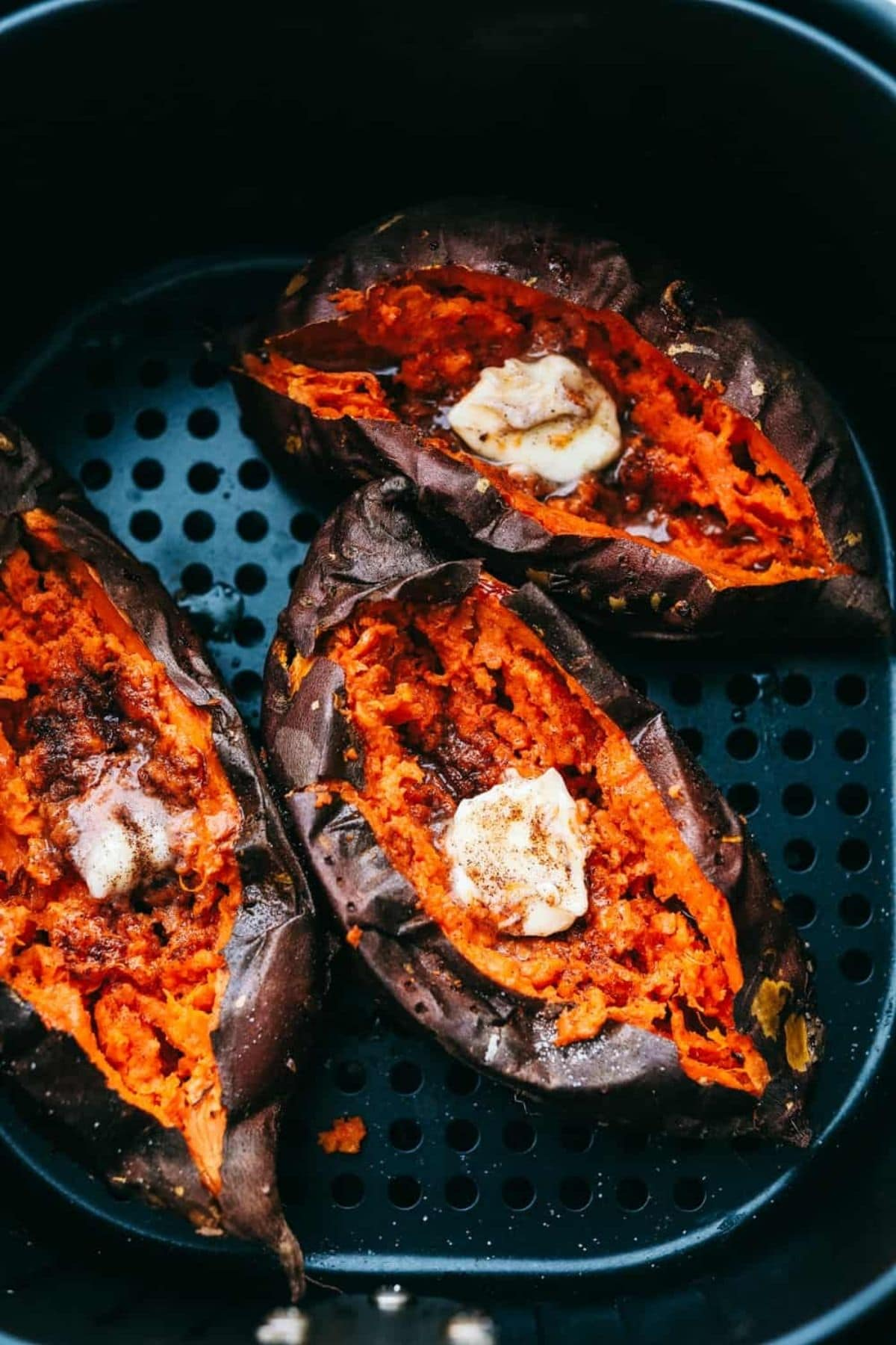 Sweet potatoes in air fryer basket with butter