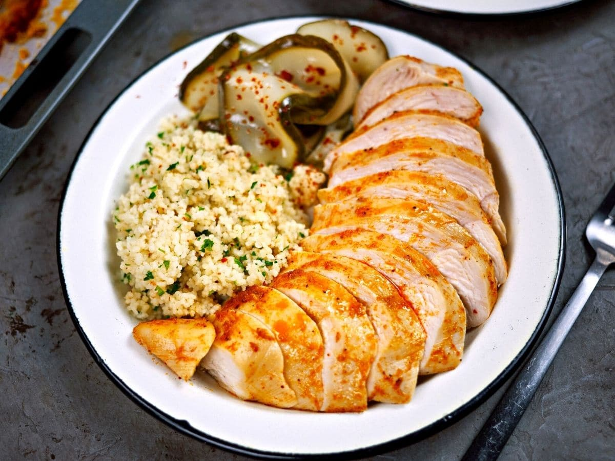 White plate with chicken breasts rice and pickles on gray counter