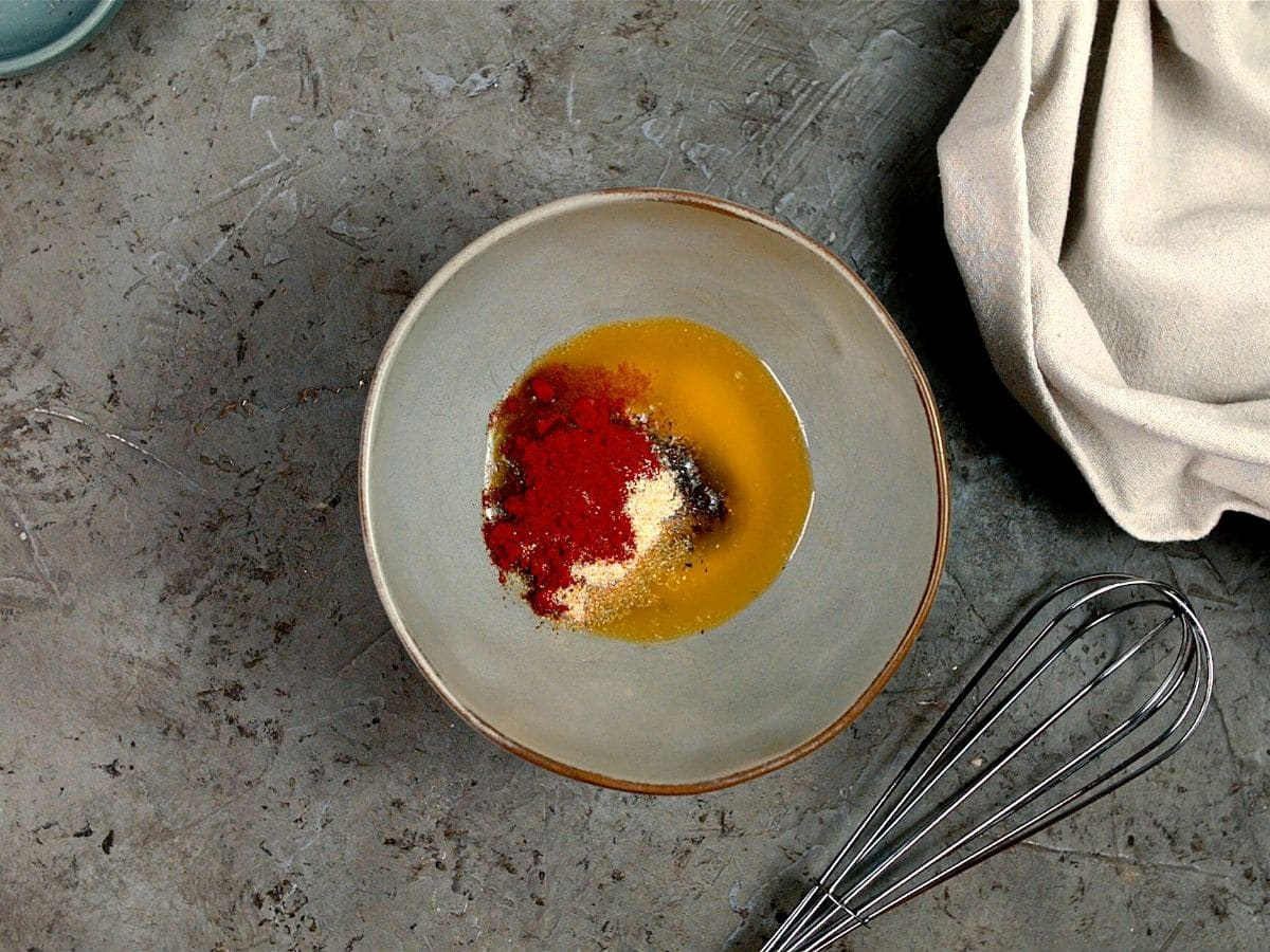 Gray bowl of melted butter with paprika