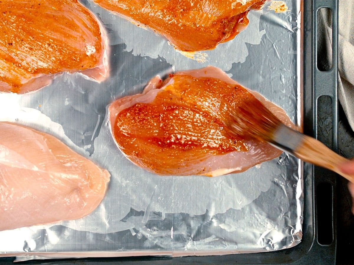 Chicken breasts on baking sheet brushed with paprika butter