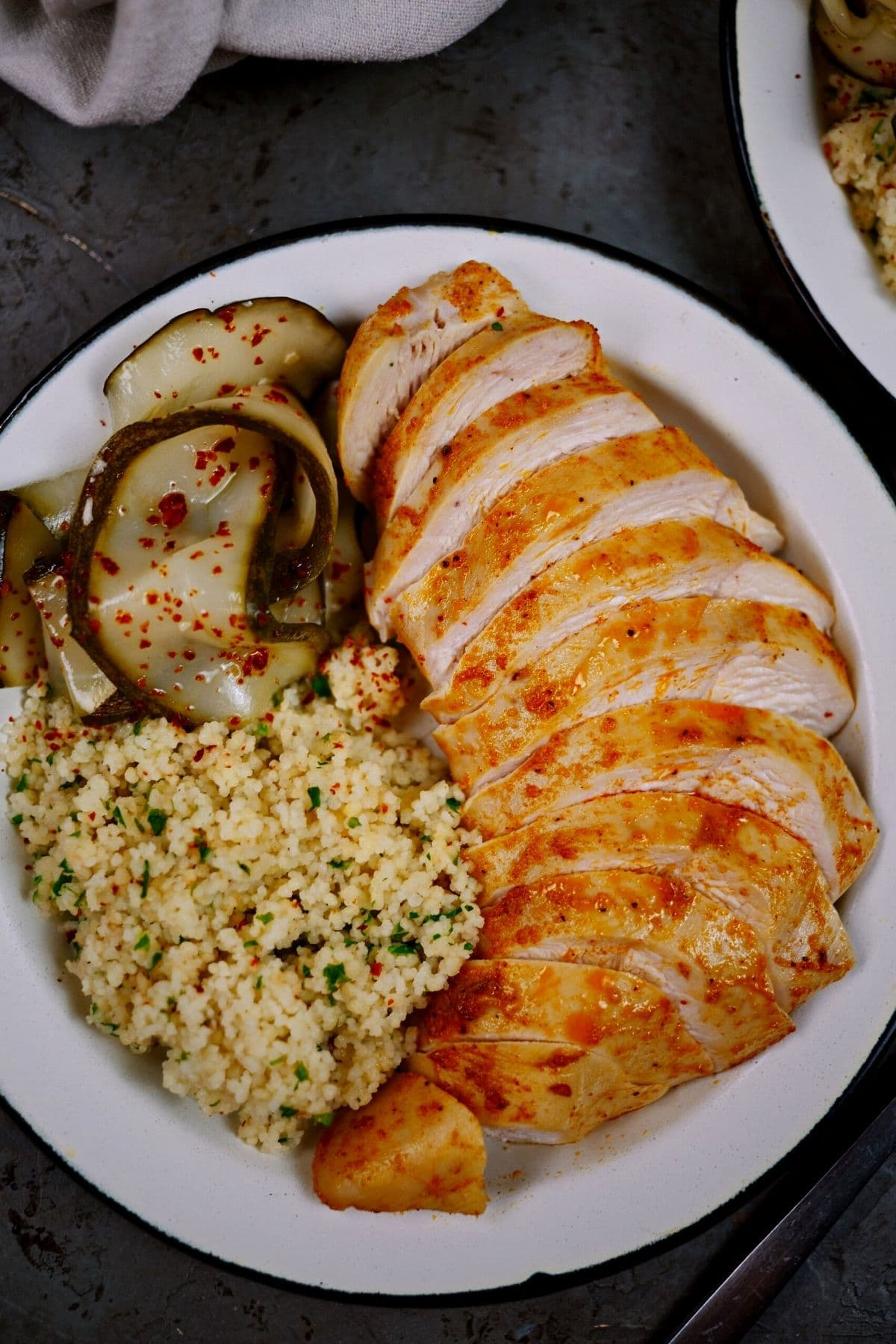Sliced chicken breast on white plate with rice and pickle