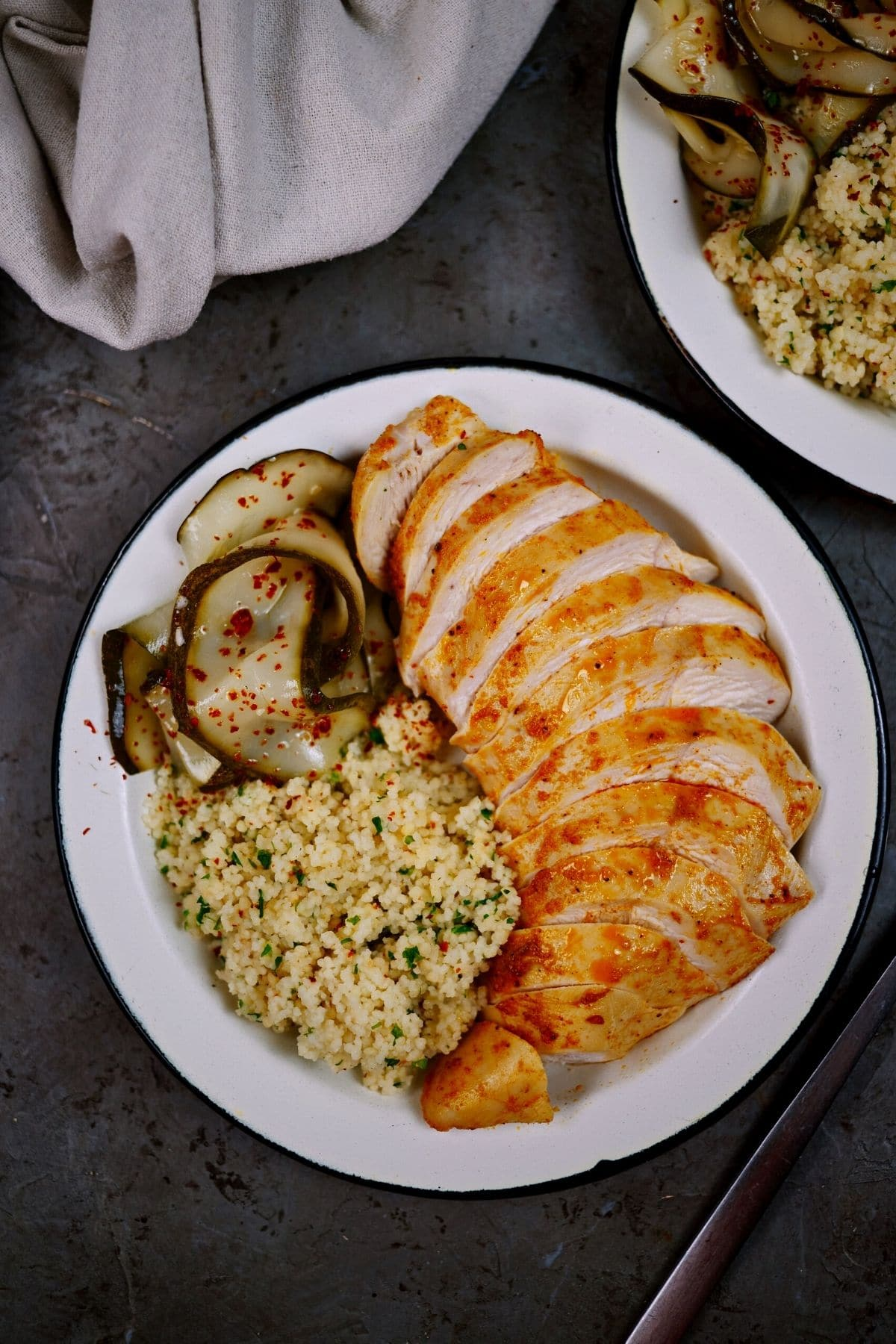 Pickles rice and chicken on white plate sitting on gray table