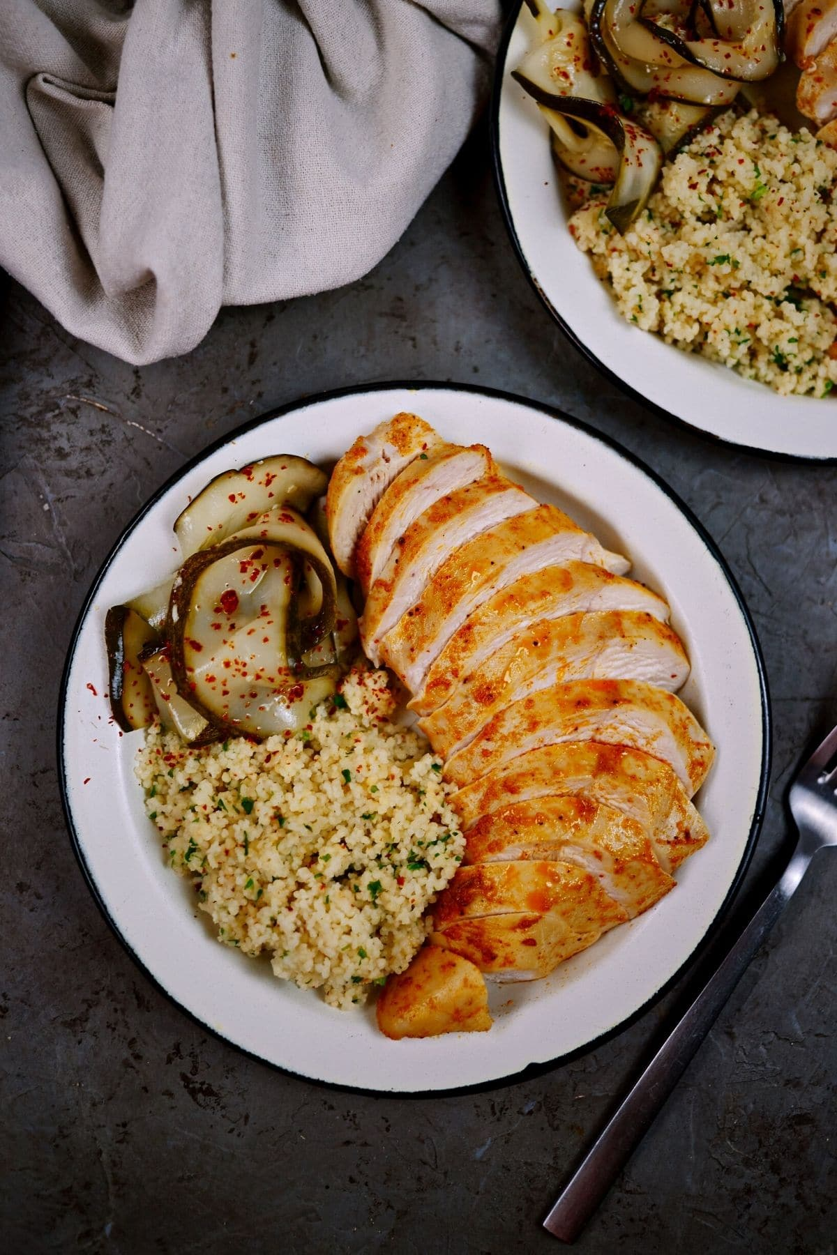 Two plates of chicken and rice on gray table