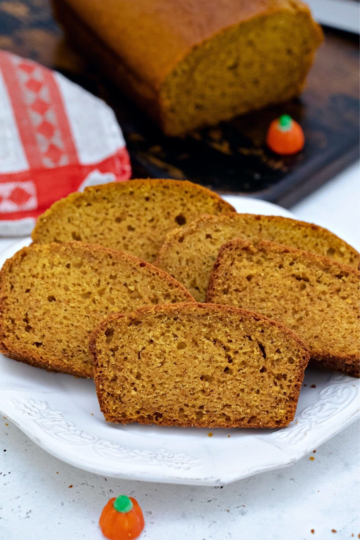 Pumpkin bread slices on white plate next to red and white napkin
