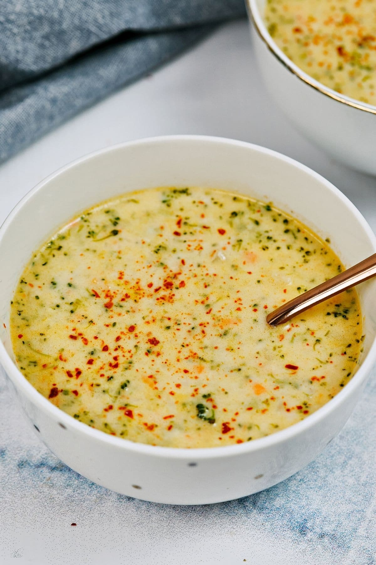 Two white bowls of broccoli soup on white table