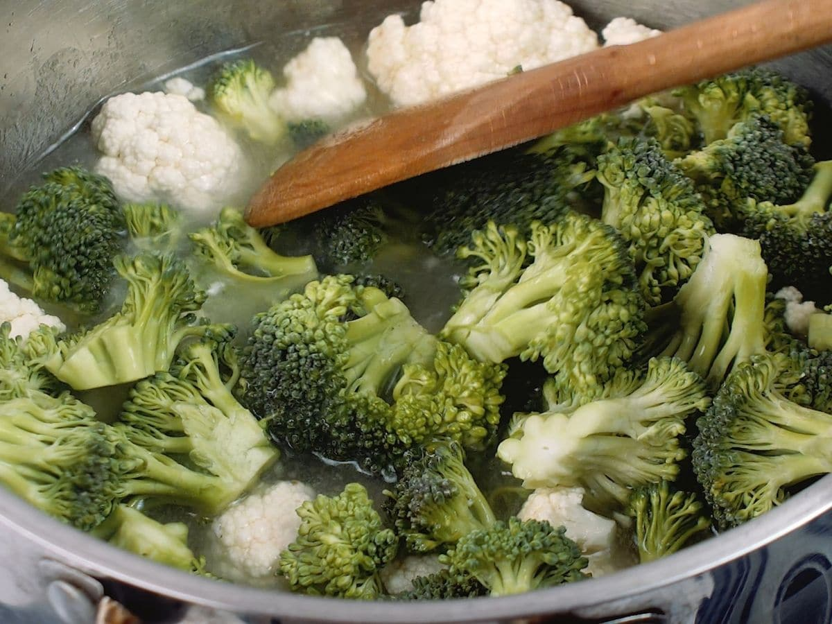 Wooden spoon pressing broccoli and cauliflower into pot