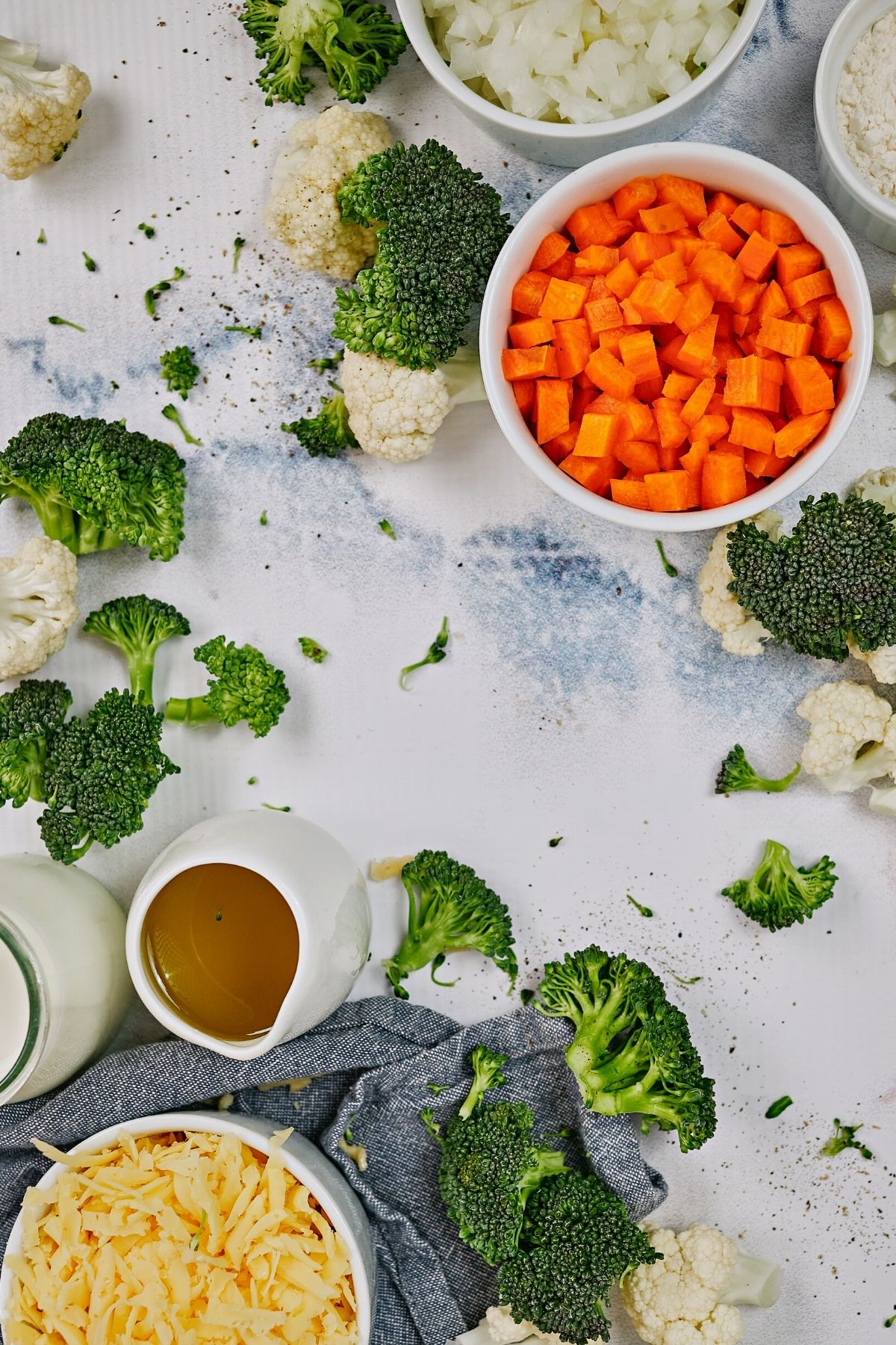 White counter with broccoli carrots and cheese in bowls