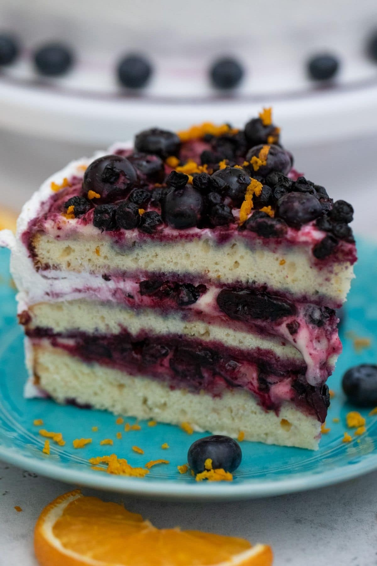 Tall slice of layer cake with berries on teal plate by orange slice