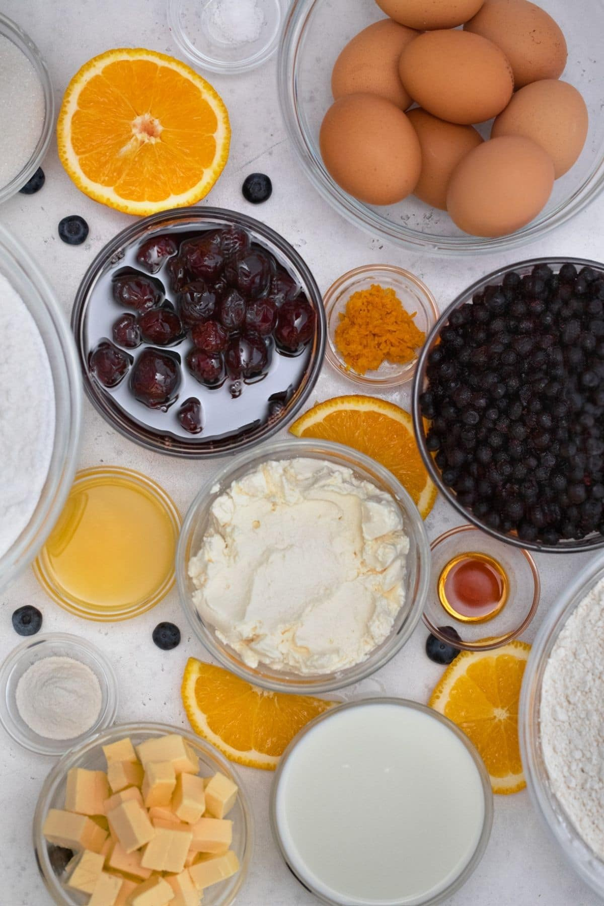 Ingredients for blueberry layer cake in glass bowls on white table