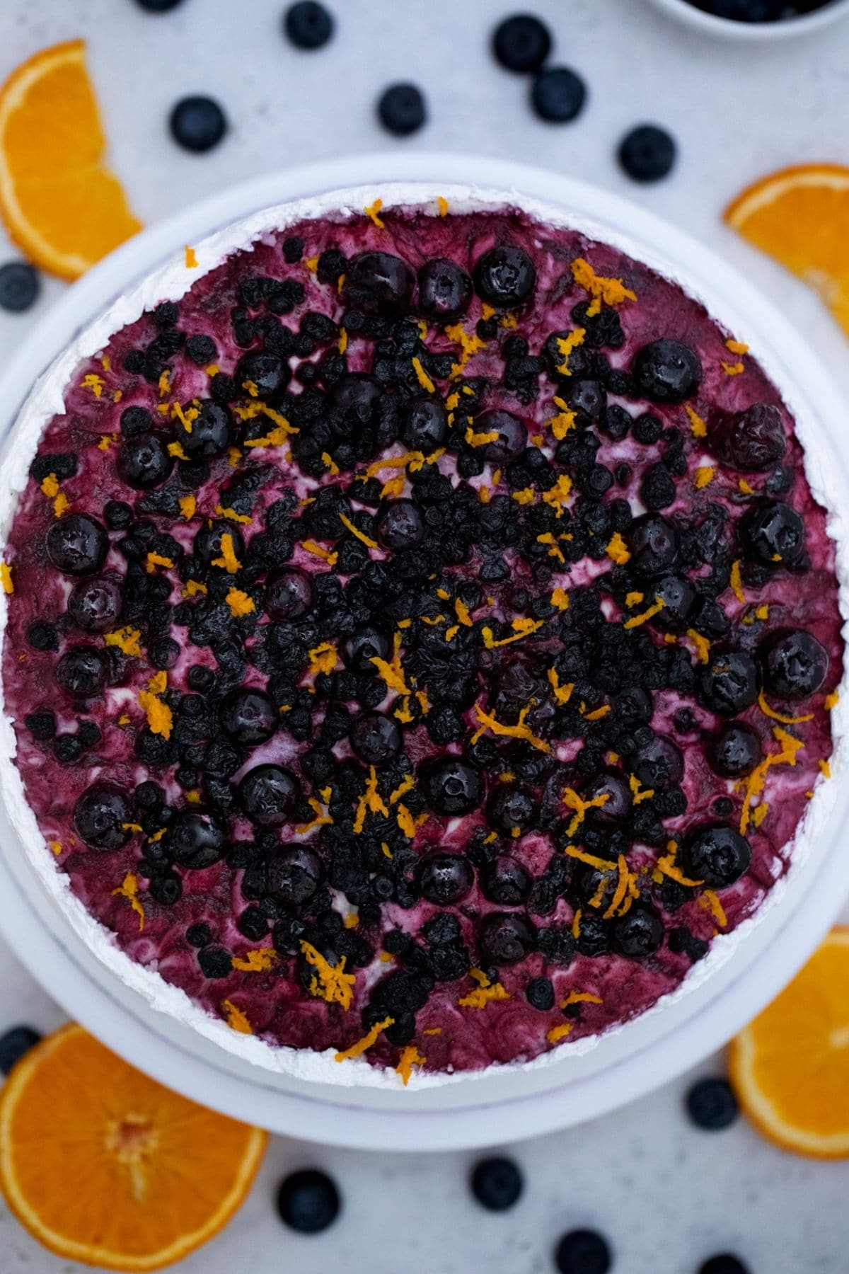 Cake topped with blueberry and cranberry compote and orange zest