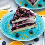 Slice of berry layer cake on light teal plate with blueberries and orange zest