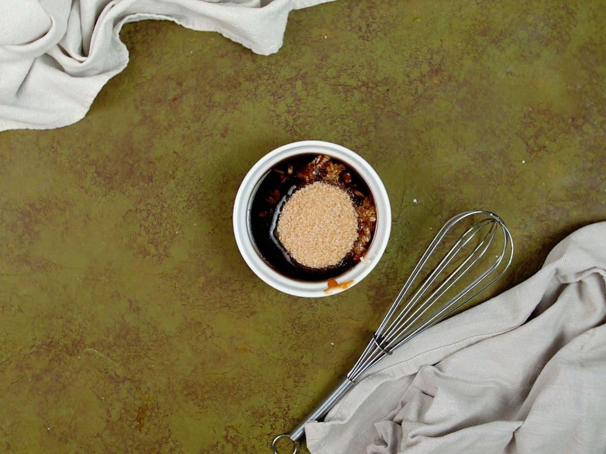 White ramekin of sauce with sugar on top