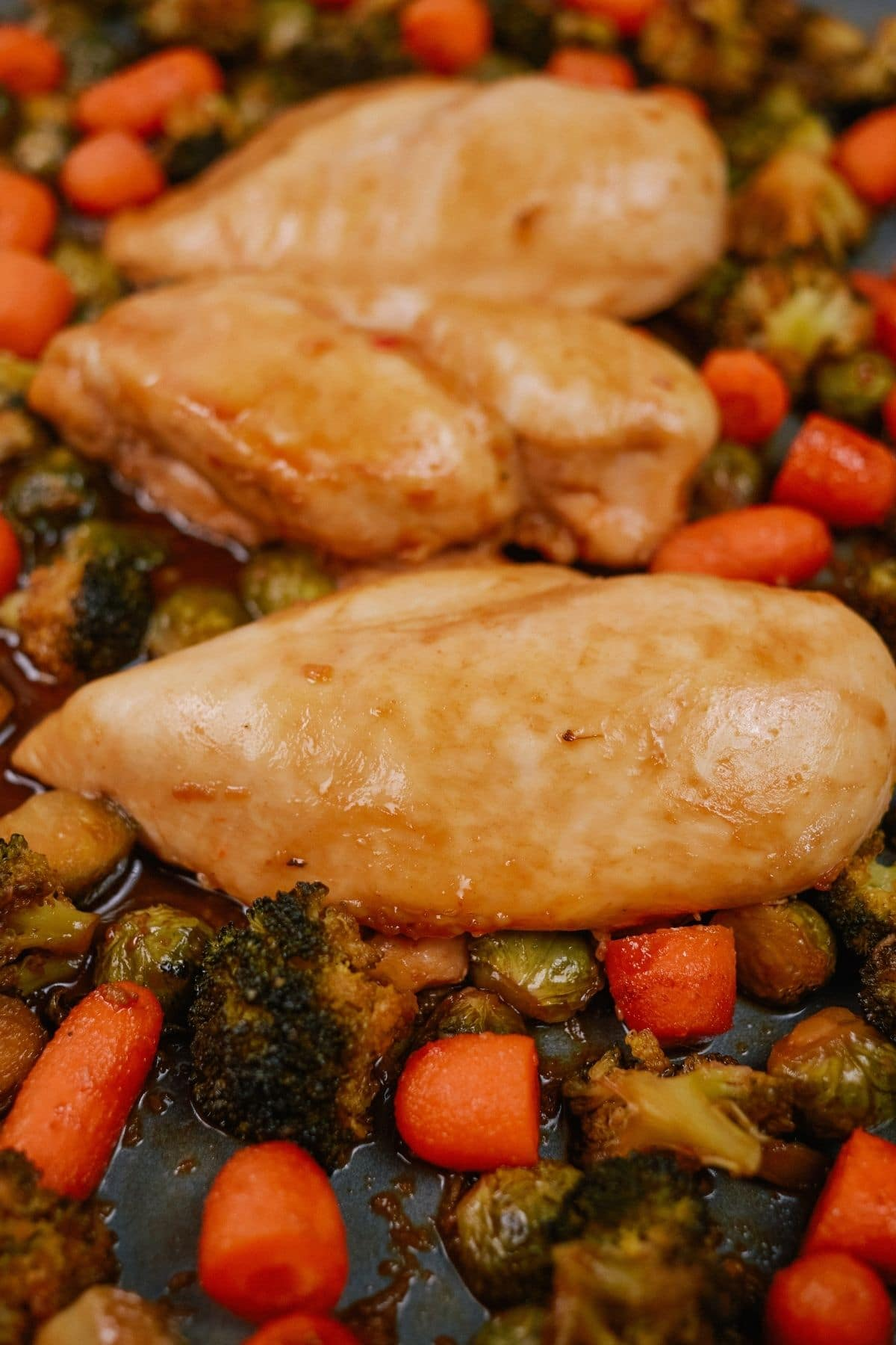 Chicken breasts on top of vegetables on baking sheet