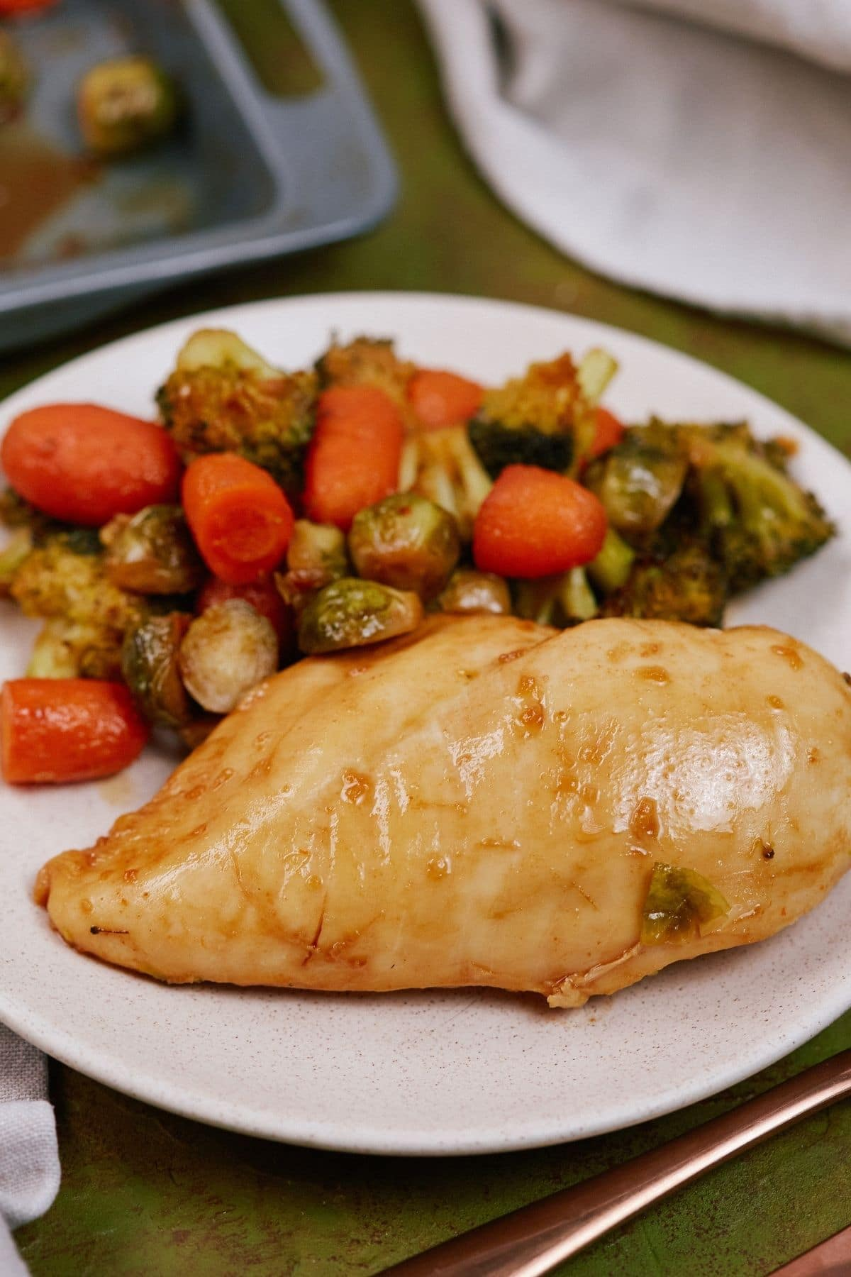 Chicken and vegetables on plate next to baking sheet