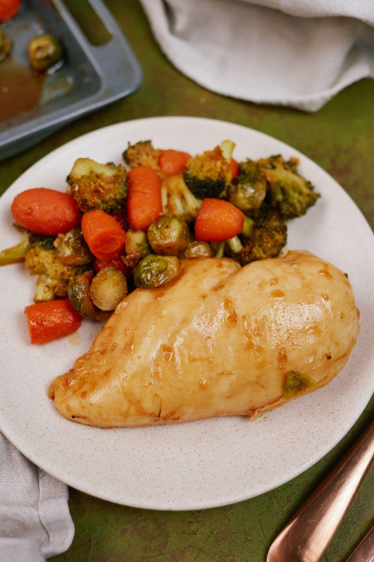 White plate with chicken breast and vegetables on green tablecloth