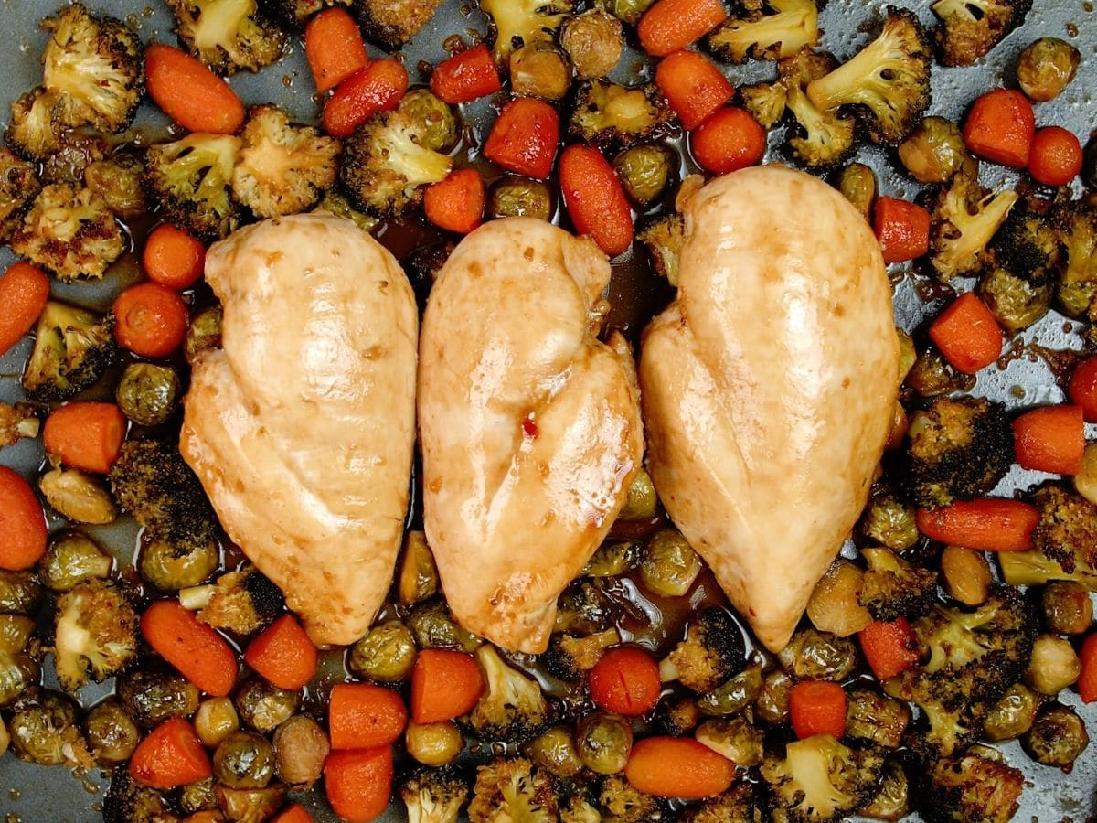 Sheet pan with carrots broccoli and brussels sprouts underneath baked chicken breasts