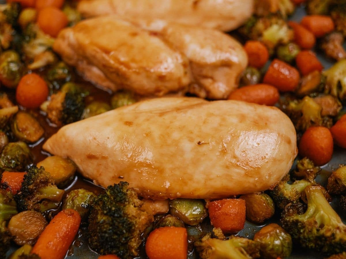 Close image of baked chicken breast on top of carrots and broccoli